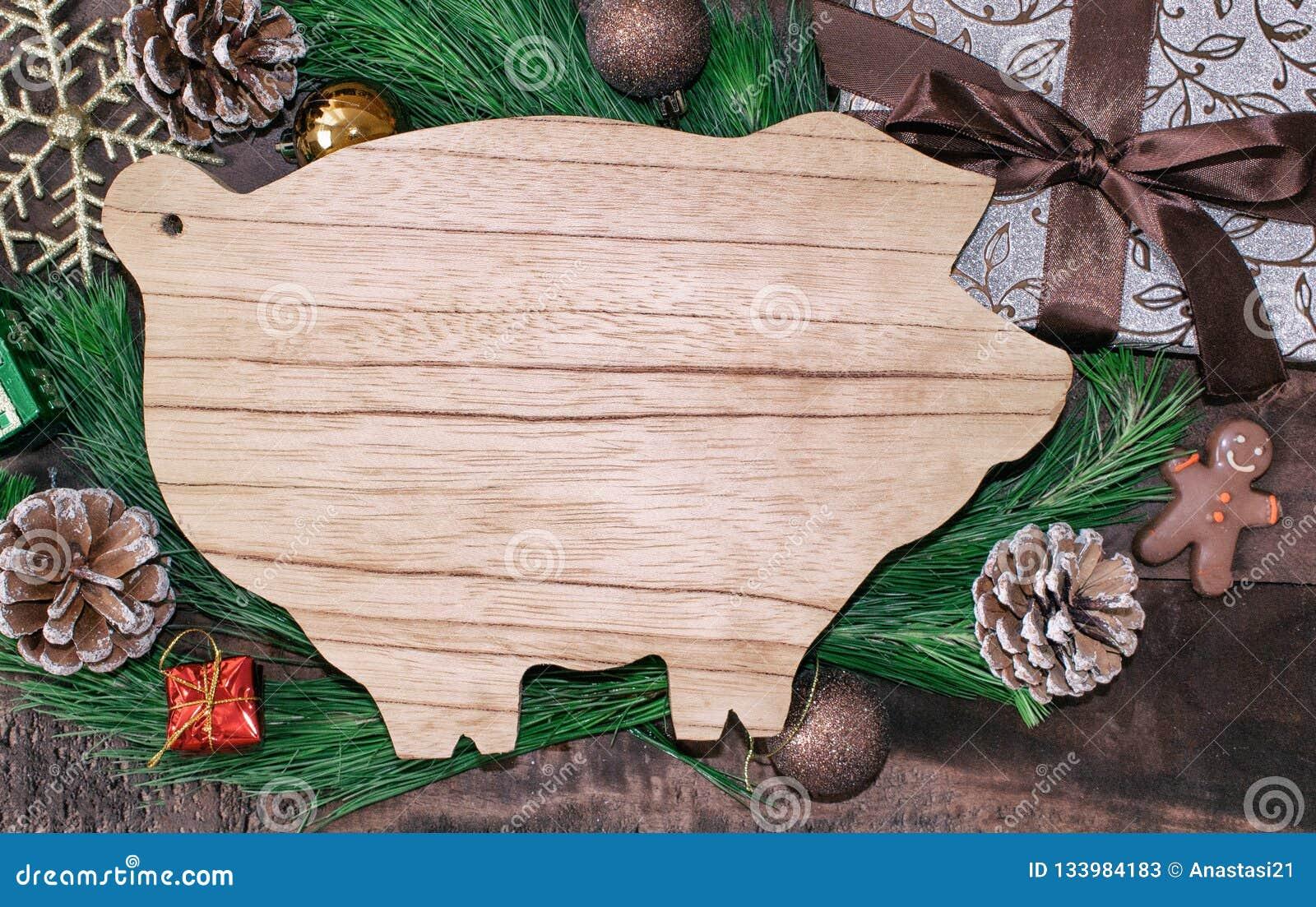 Подготовки рождества, разделочная доска в форме свиней, ветви ели, конусы и украшения Новый Год свиньи на китайце