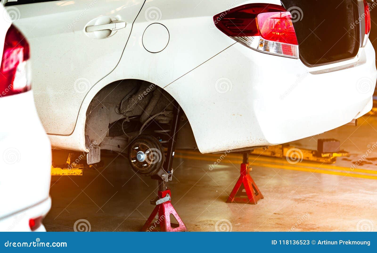Поднят и изменять белый автомобиль припаркованный в мастерской гаража автошина и обслуживание Автоматическое предприятие сферы об