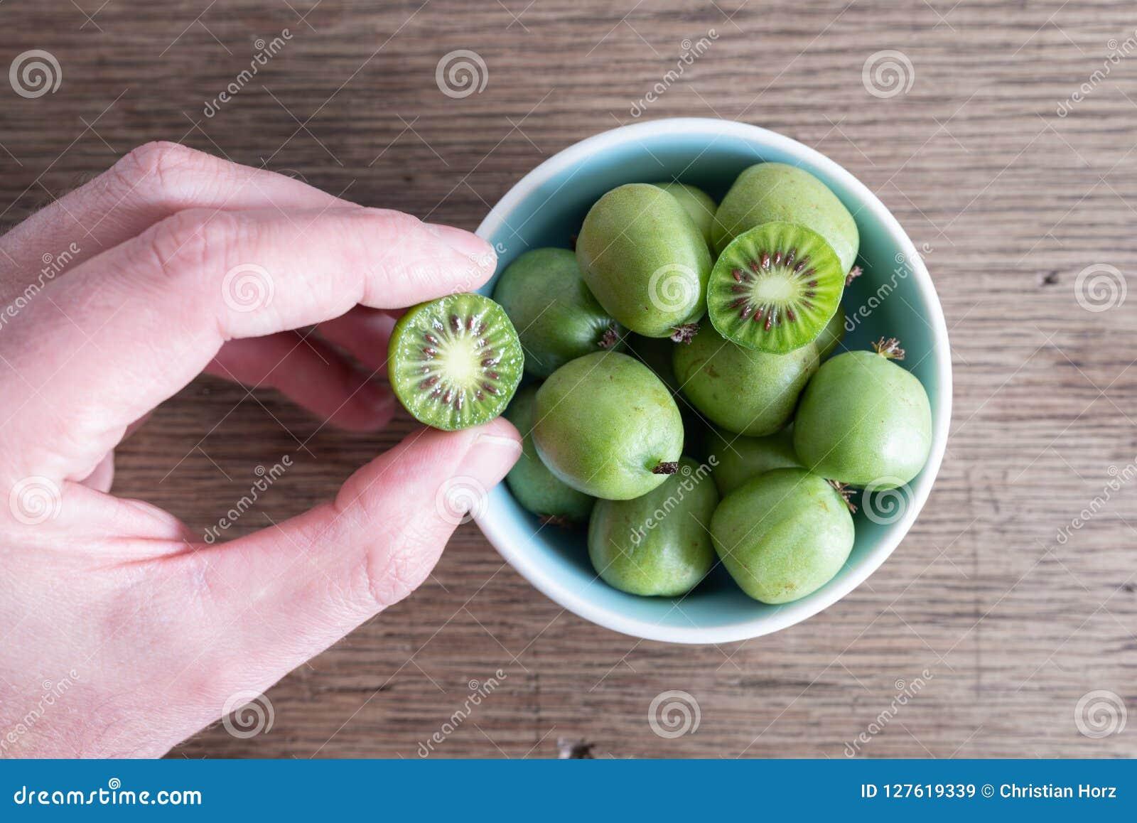 Подрезанная рука выбирая выносливые плодоовощ кивиа или ягоду кивиа от керамического шара на таблице