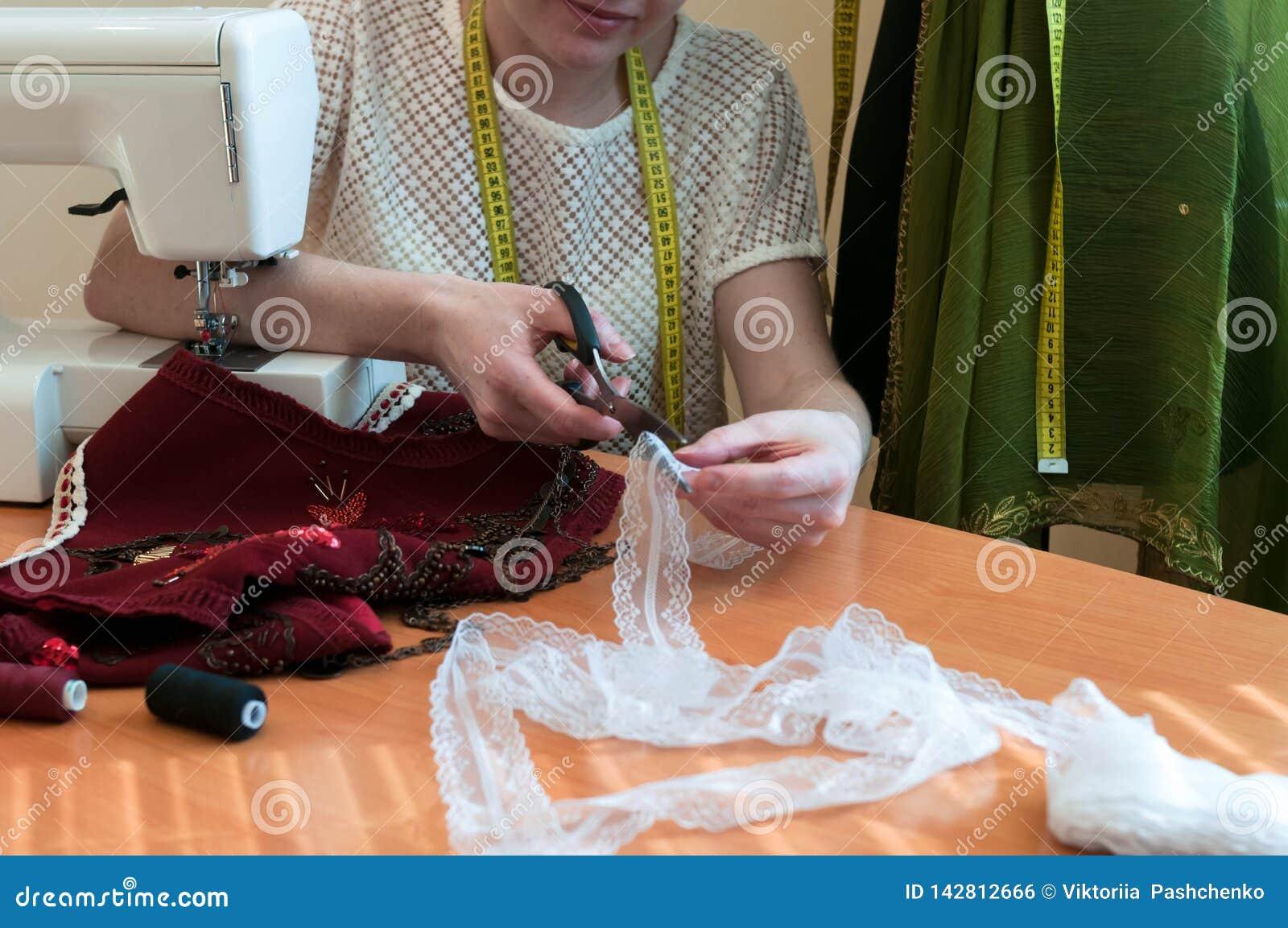 Подрезанный взгляд белошвейки сидя на таблице со швейной машиной и режа шнурок