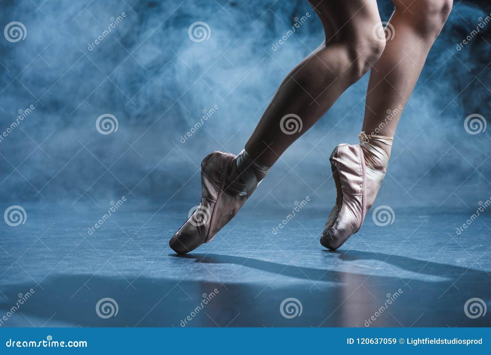 подрезанный взгляд танцев балерины в ботинках pointe в темной студии