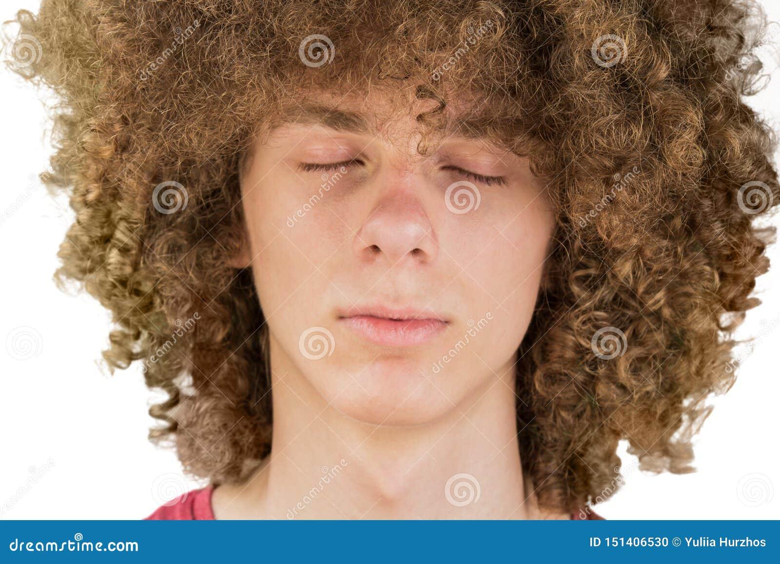 Подрезанный портрет молодого курчавого европейского человека с длинным вьющиеся волосы и закрытые глаза закрывают вверх очень соч