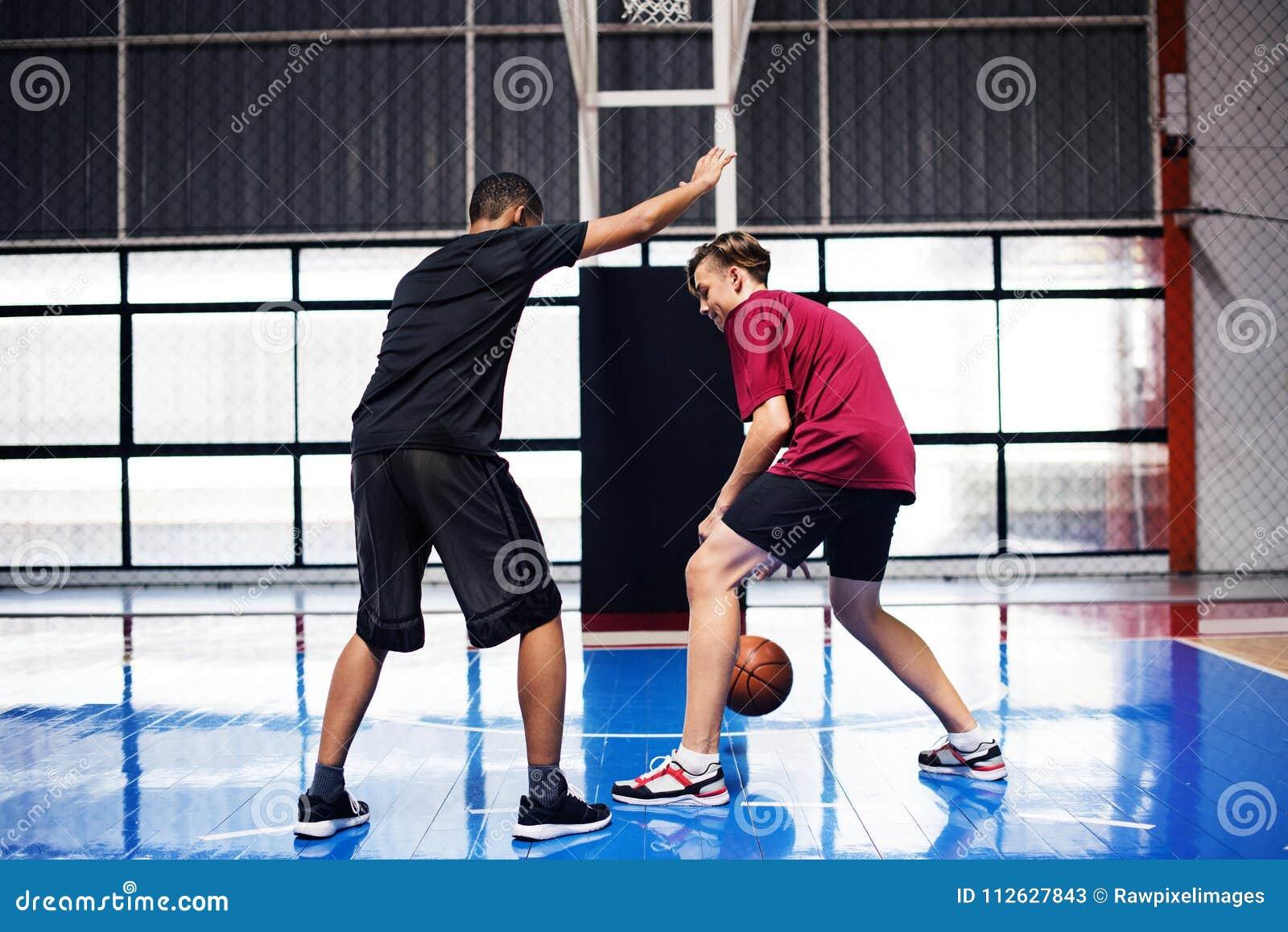 2 подростка играя баскетбол совместно на суде