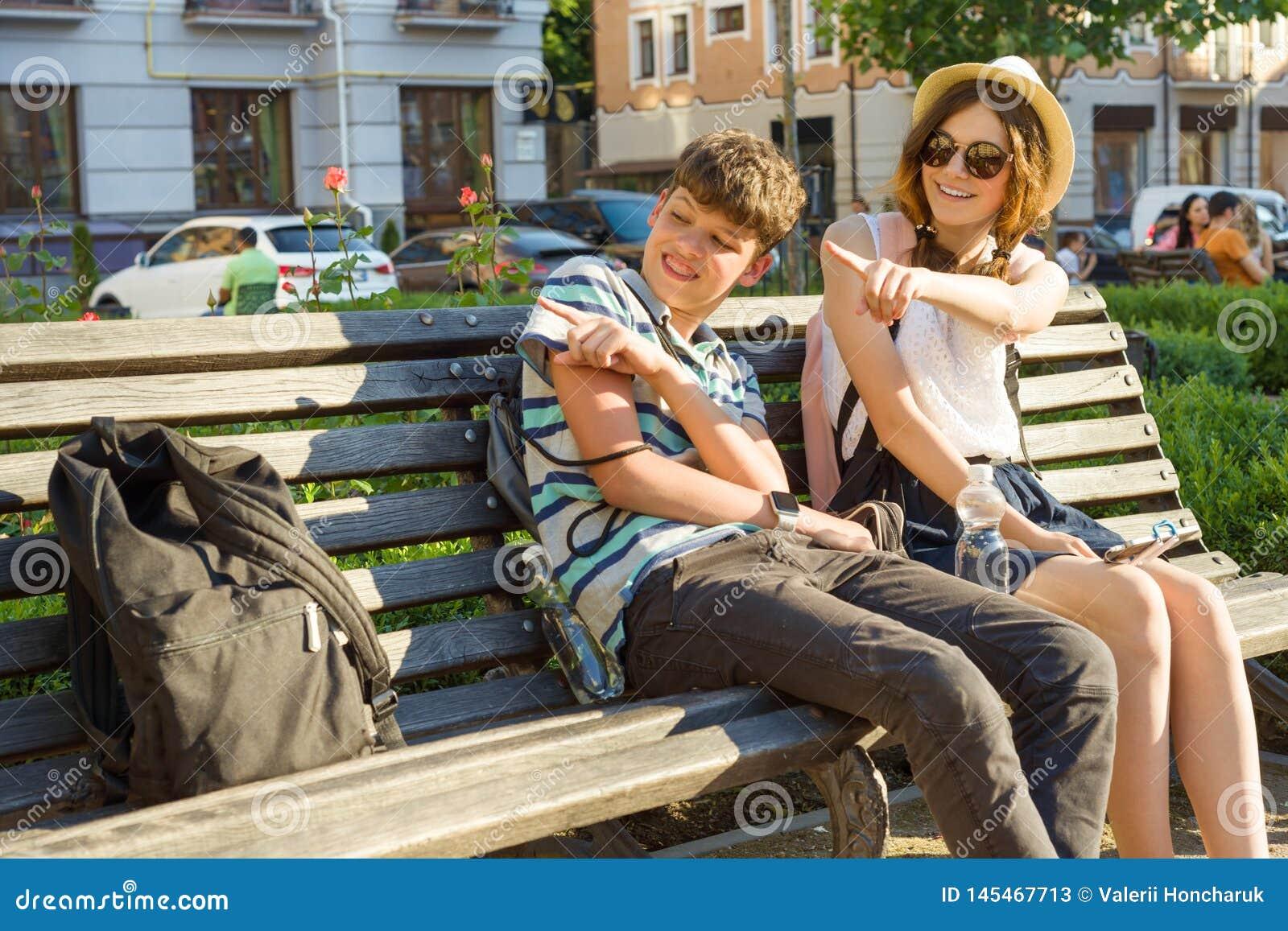 Подростковые друзья девушка и мальчик сидя на стенде в городе, усмехающся, говорить, смотря в телефоне Приятельство и концепция л