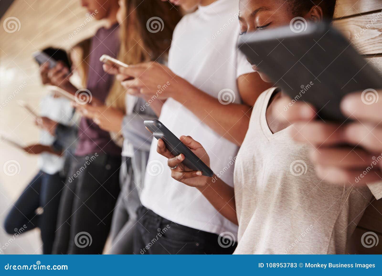 Подростковые студенты используя приборы цифров на кампусе коллежа