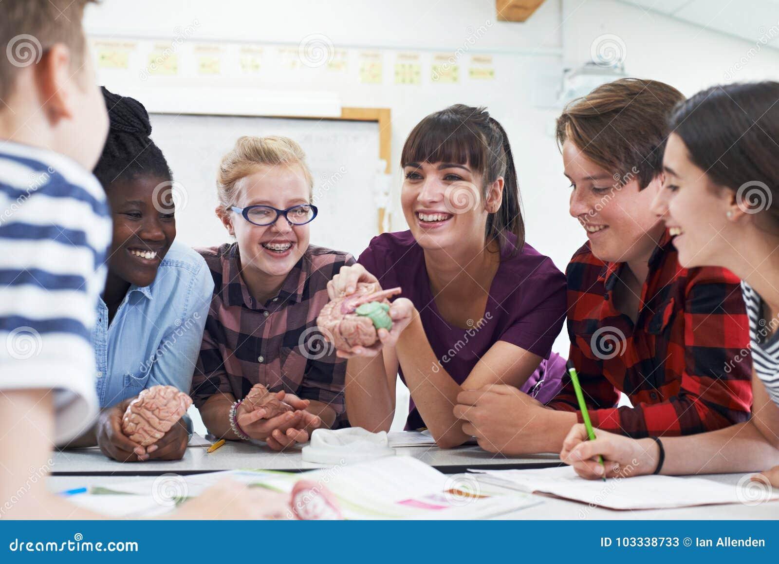 Подростковые студенты с учителем в уроке биологии