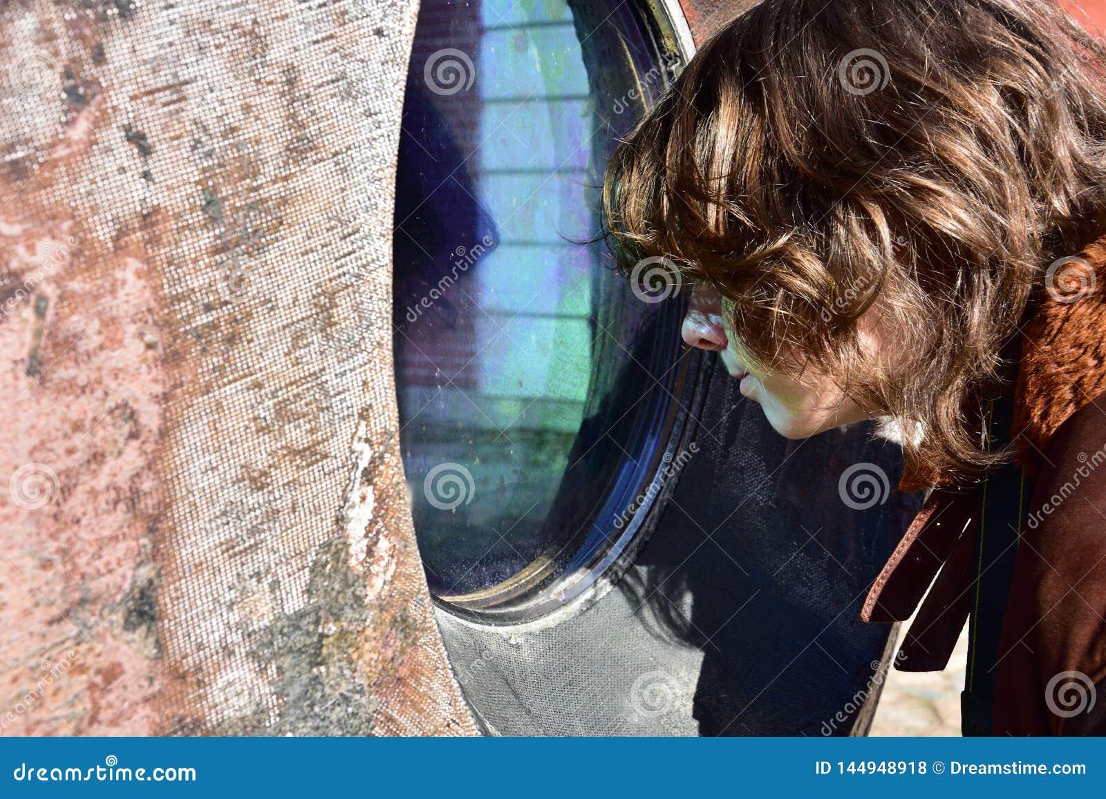 Подросток всматривается на зеленоголубом окне