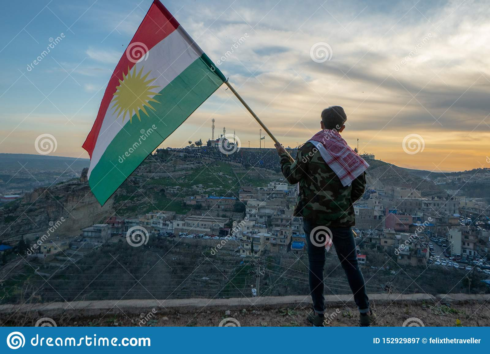 Подросток держа флаг Курдистана в северном Ираке на времени захода солнца