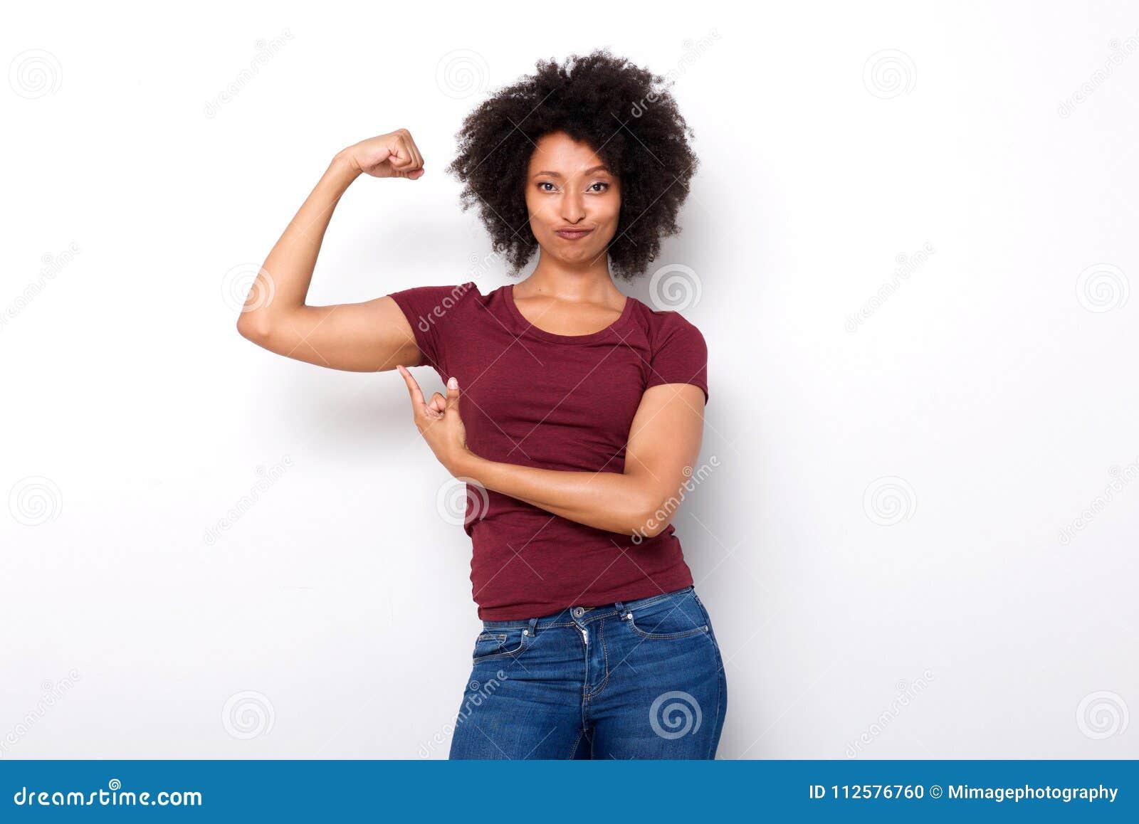 Подходящая молодая африканская женщина указывая на руку muscles на белой предпосылке