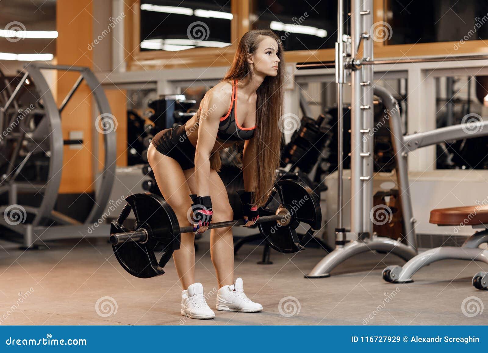 Подходящая молодая женщина делает тренировку deadlift с штангой в спортзале Спорт, фитнес, powerlifting и концепция людей