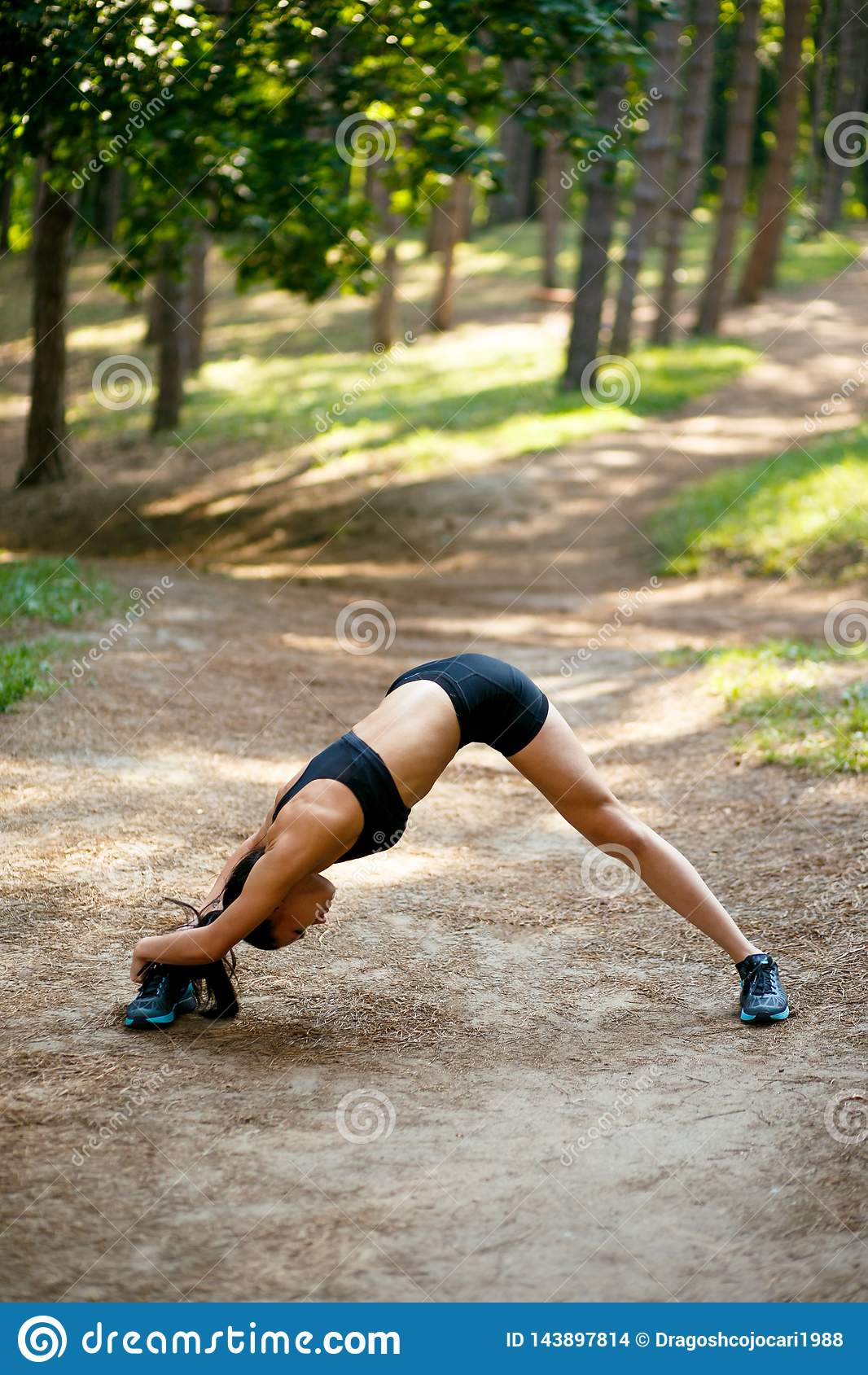 Подходящая, мышечная девушка в sportswear делая протягивающ тренировки с ее ногами боковыми, на зеленой предпосылке парка