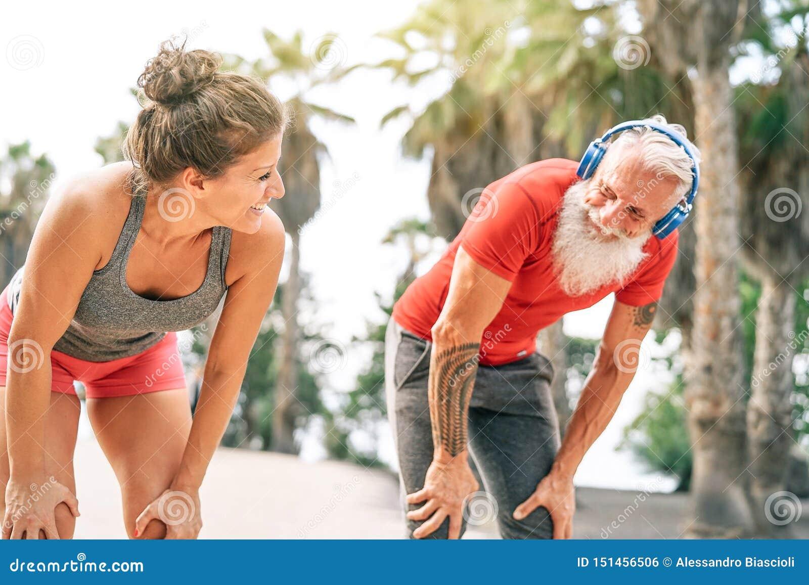 Подходящие пары друзей имея перерыв после быстрой гонки затем пляж на заходе солнца - Sporty разминке людей на открытом воздухе