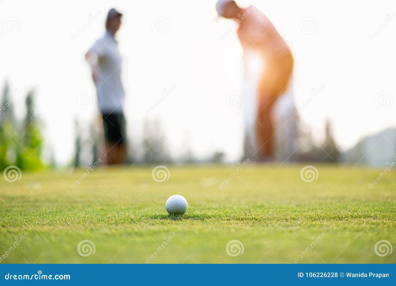Подход к шара для игры в гольф к владению на зеленом цвете Игрок гольфа пар кладя шар для игры в гольф на заднем плане
