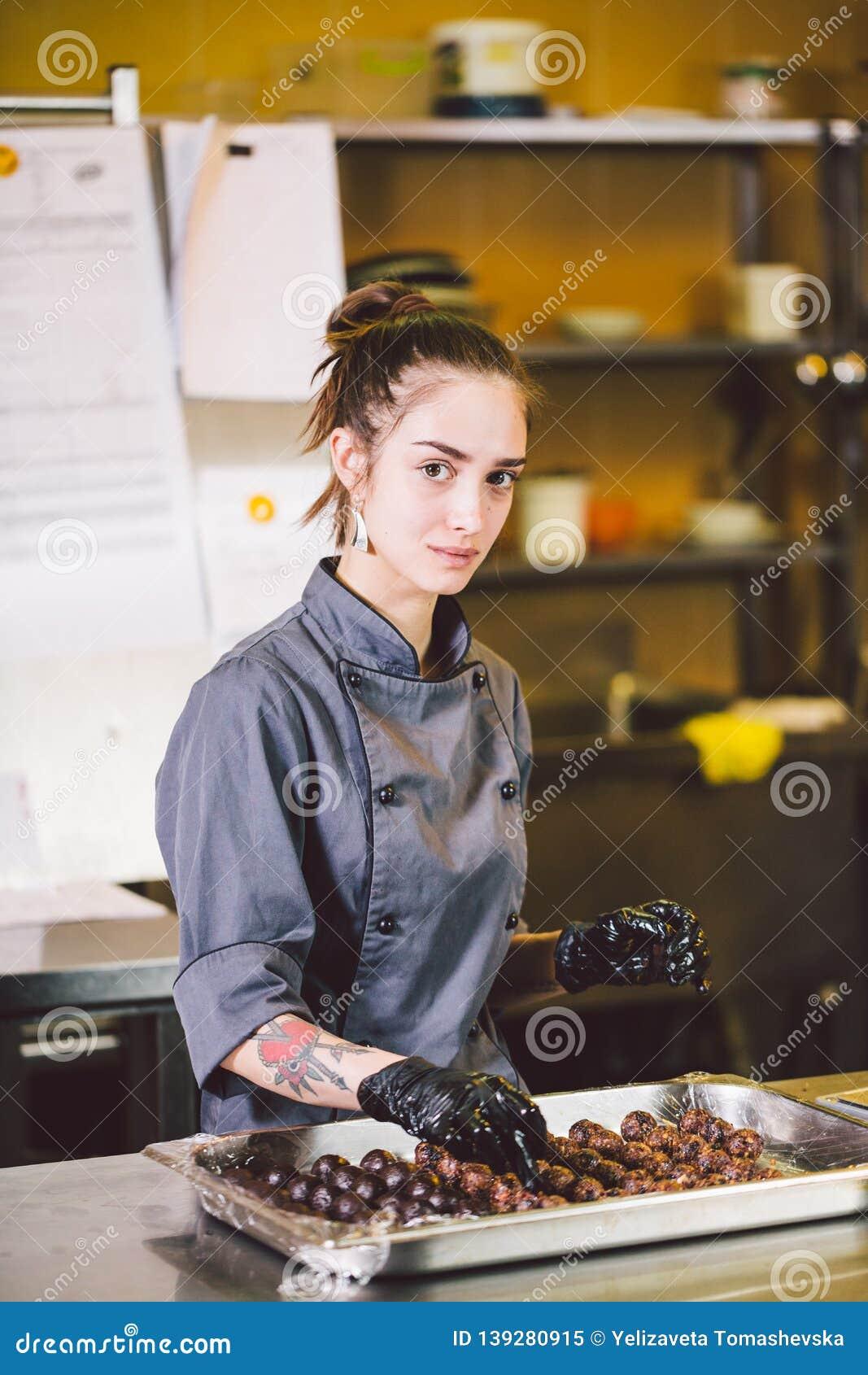 Подчиненное печенье профессии и варить молодая кавказская женщина с татуировкой кондитера в кухне ресторана подготавливая круг
