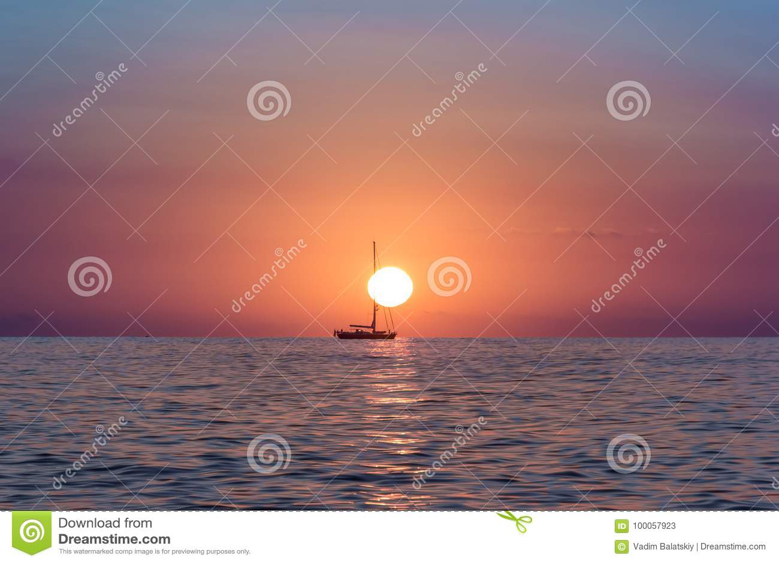 Подъем Солнця в океан при шлюпка плавая перед солнцем