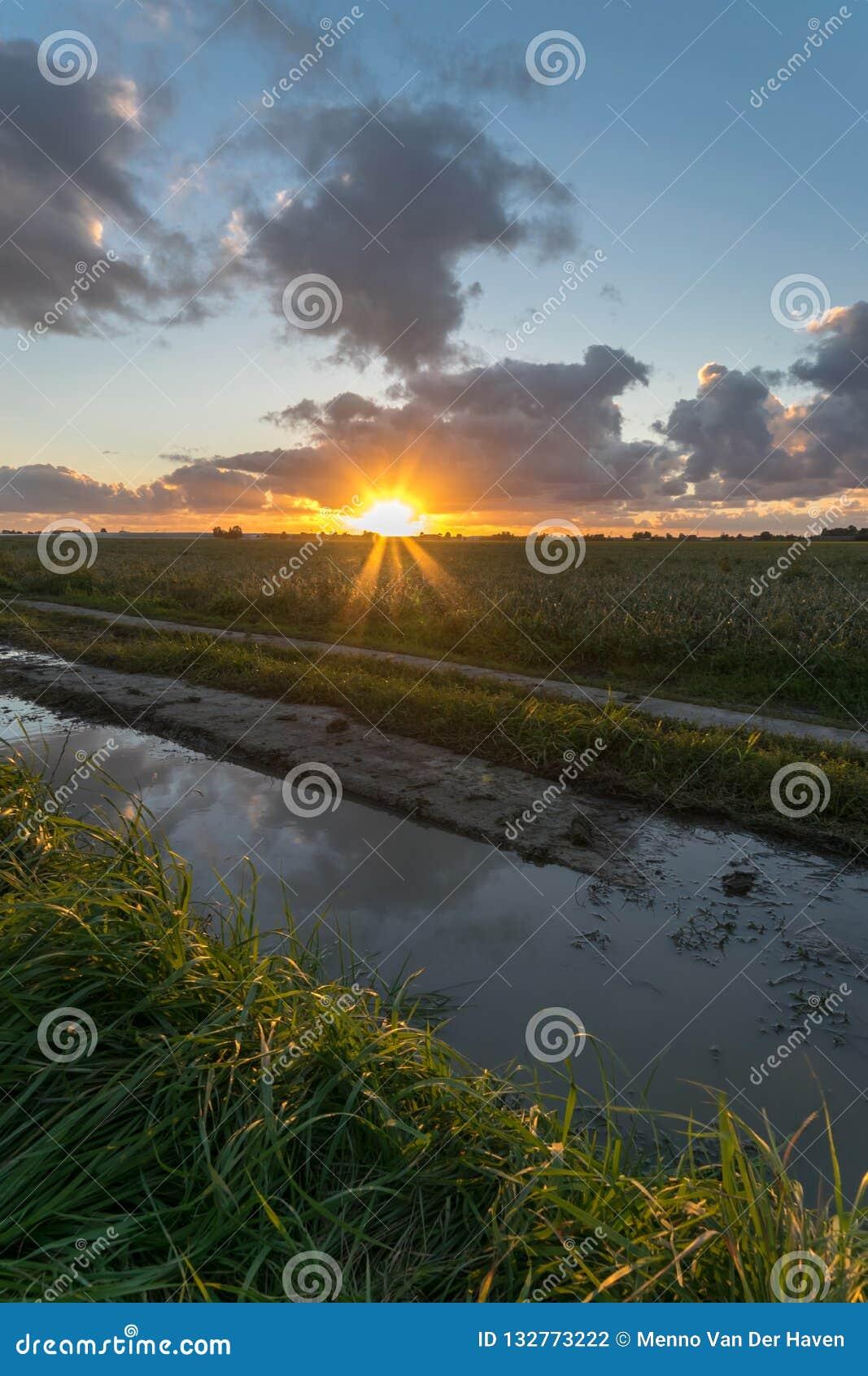 Под грядой облаков солнце устанавливает над голландской сельской местностью