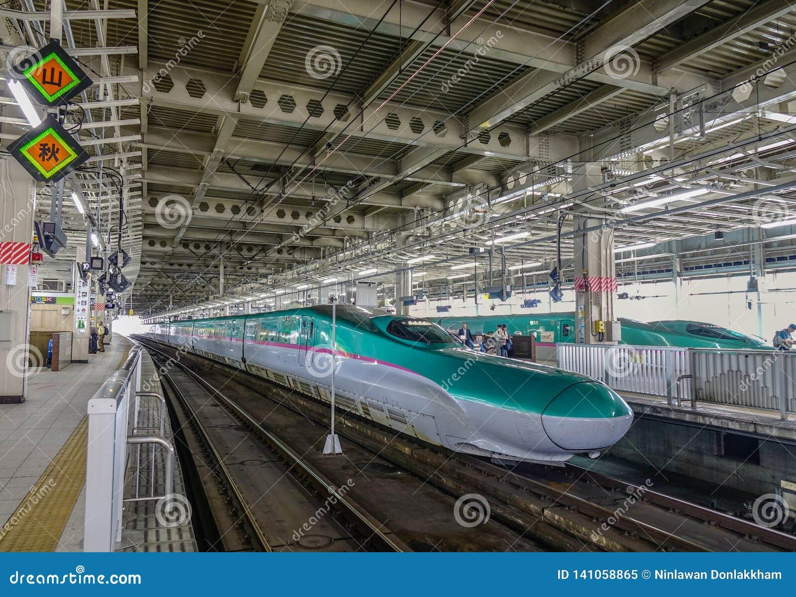 Поезд Shinkansen останавливая на железнодорожном вокзале