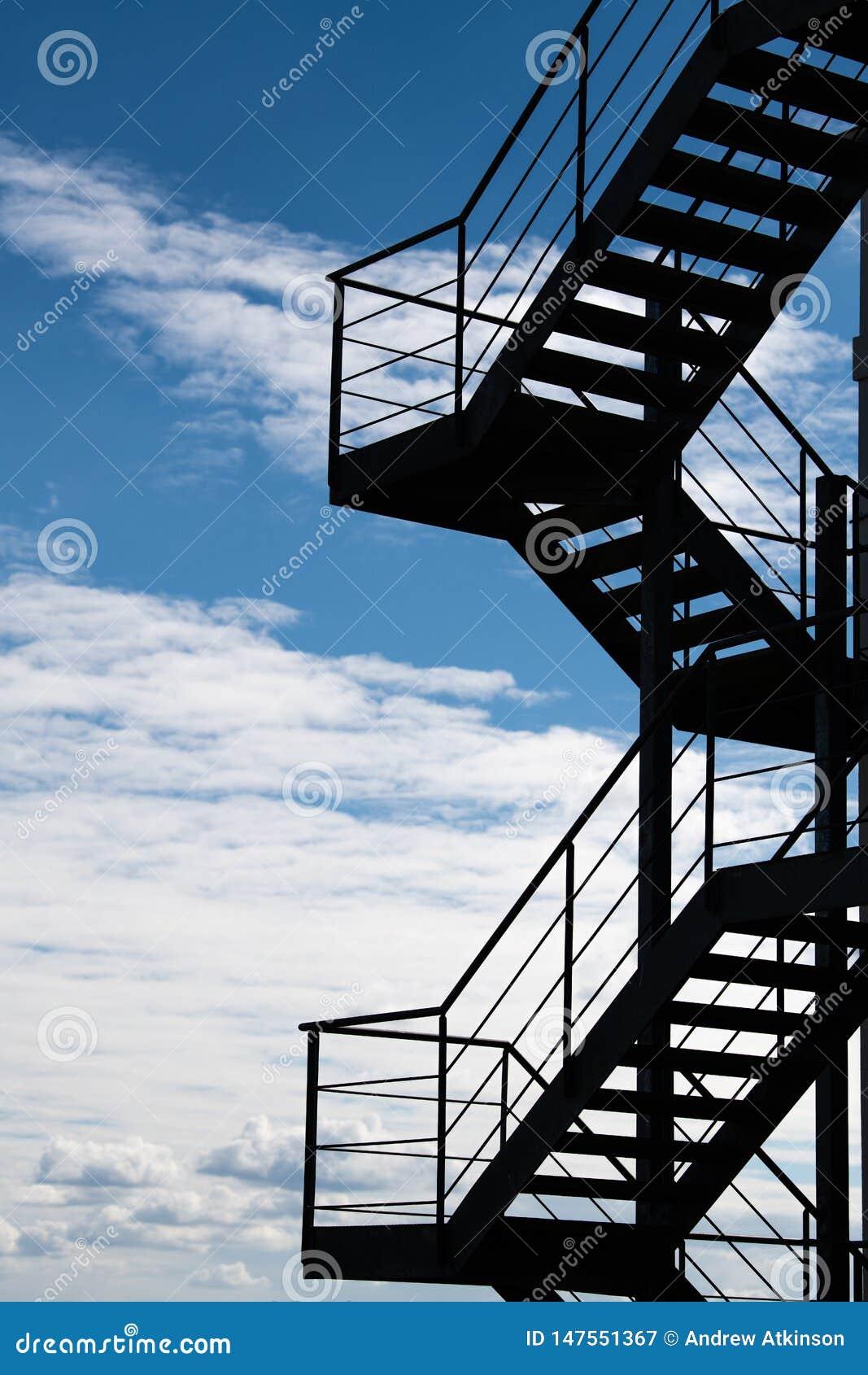 Пожарная лестница против облачного неба