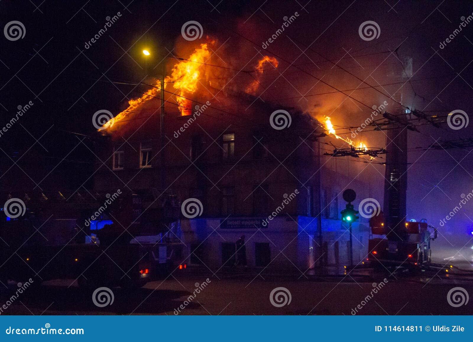 Пожарные направляют поток воды на горящем доме строить полностью ад пылать, и бой пожарного для того чтобы получить управление fl