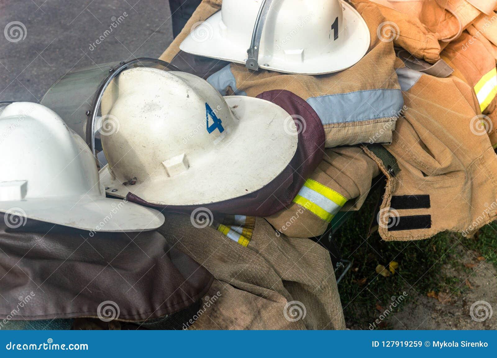 Пожарные одежды шлемов ` s пожарных на улице