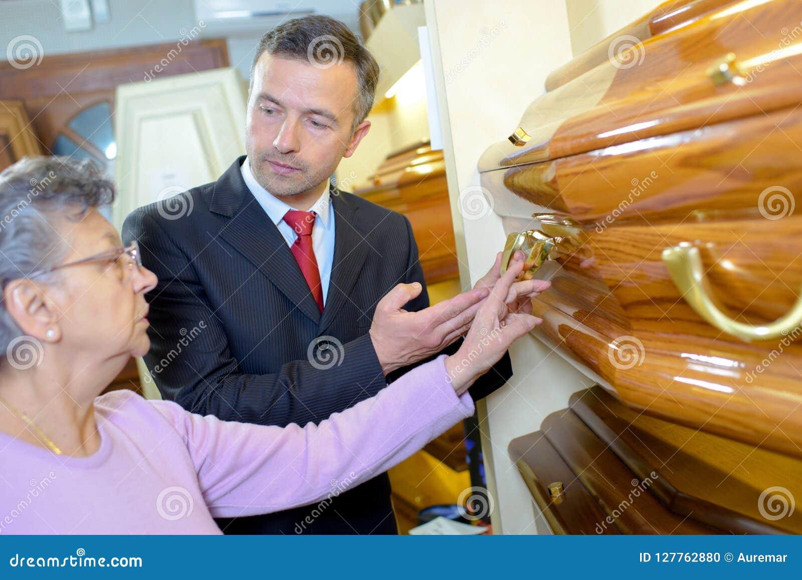 Пожилая дама при распорядитель похорон выбирая гроб