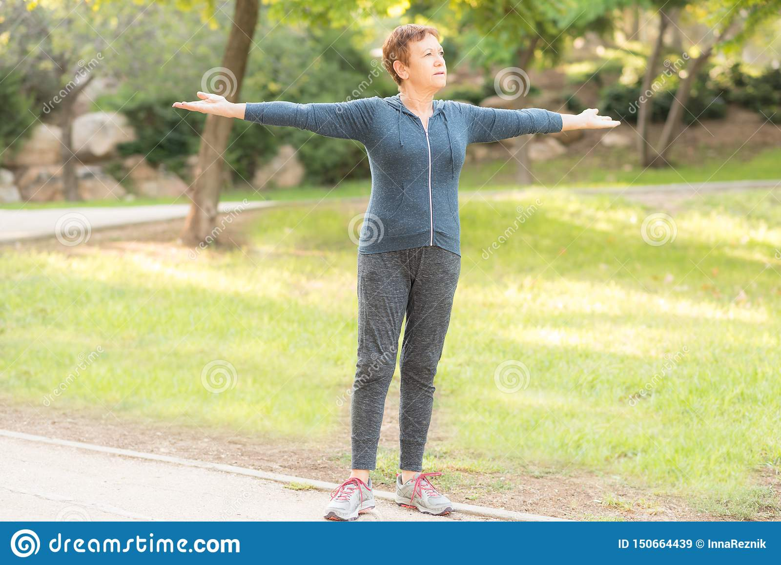 Пожилая красивая активная счастливая женщина в утре в парке осени делая тренировки спорт