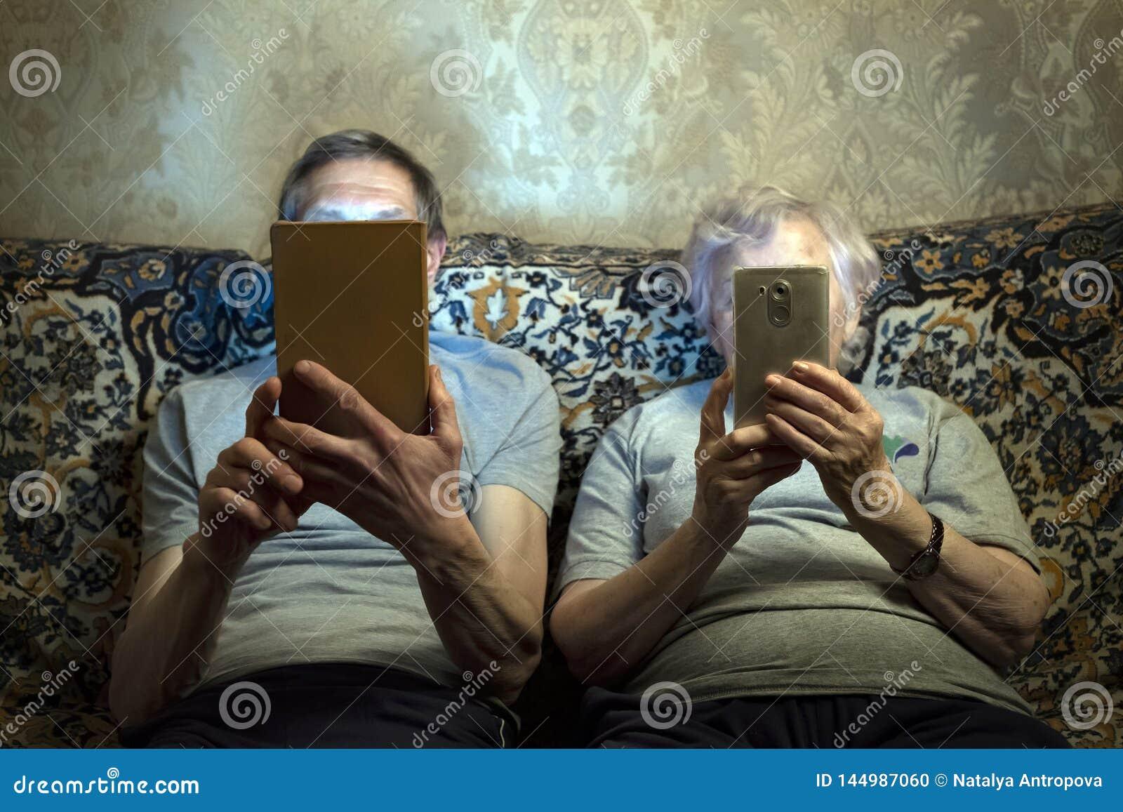 Пожилая пара сидеть на кресле с устройствами, взгляде на их закрывает