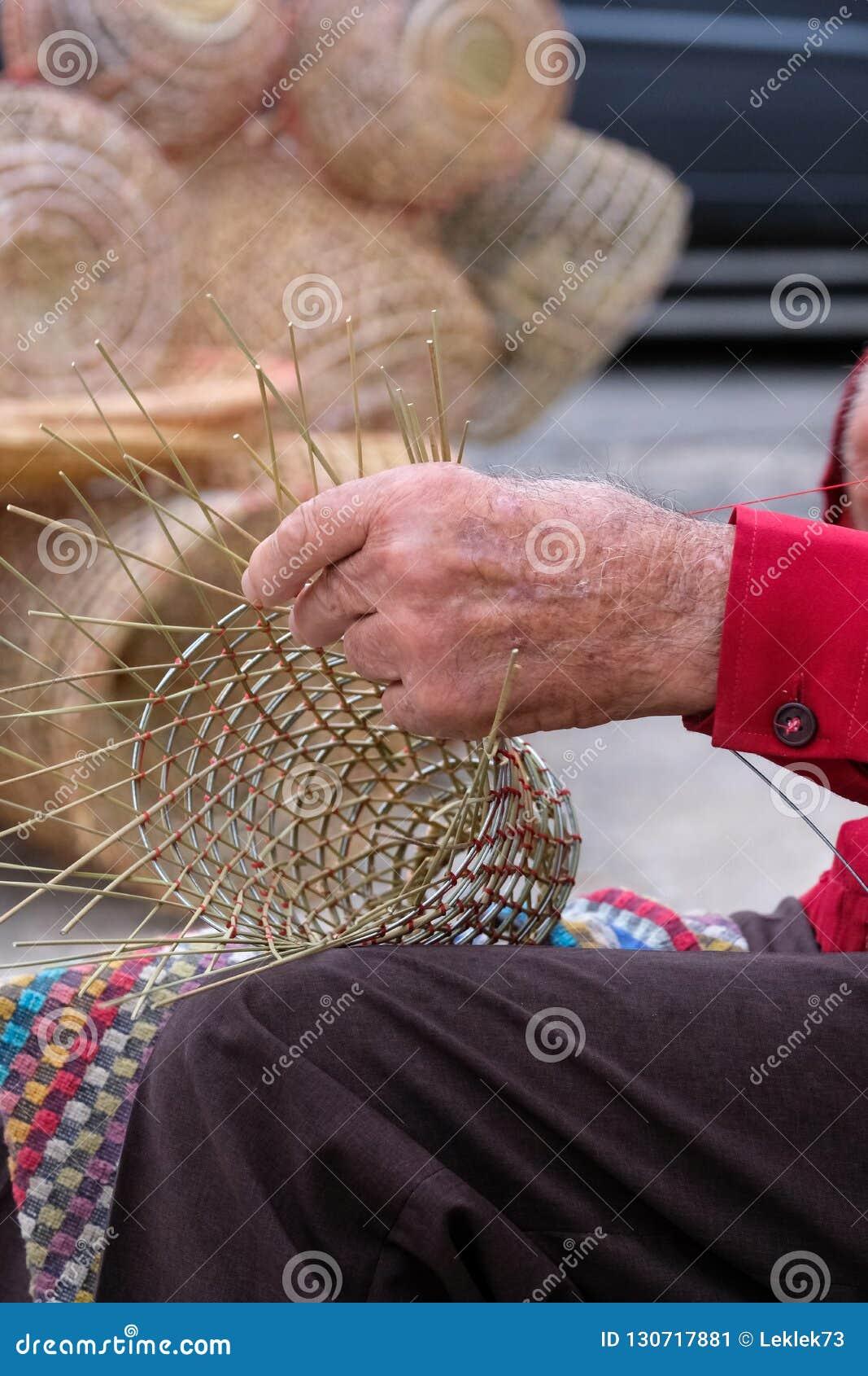 Пожилой человек делает корзины для пользы в рыбной промышленности в традиционном пути, в Gallipoli, Апулия, Италия