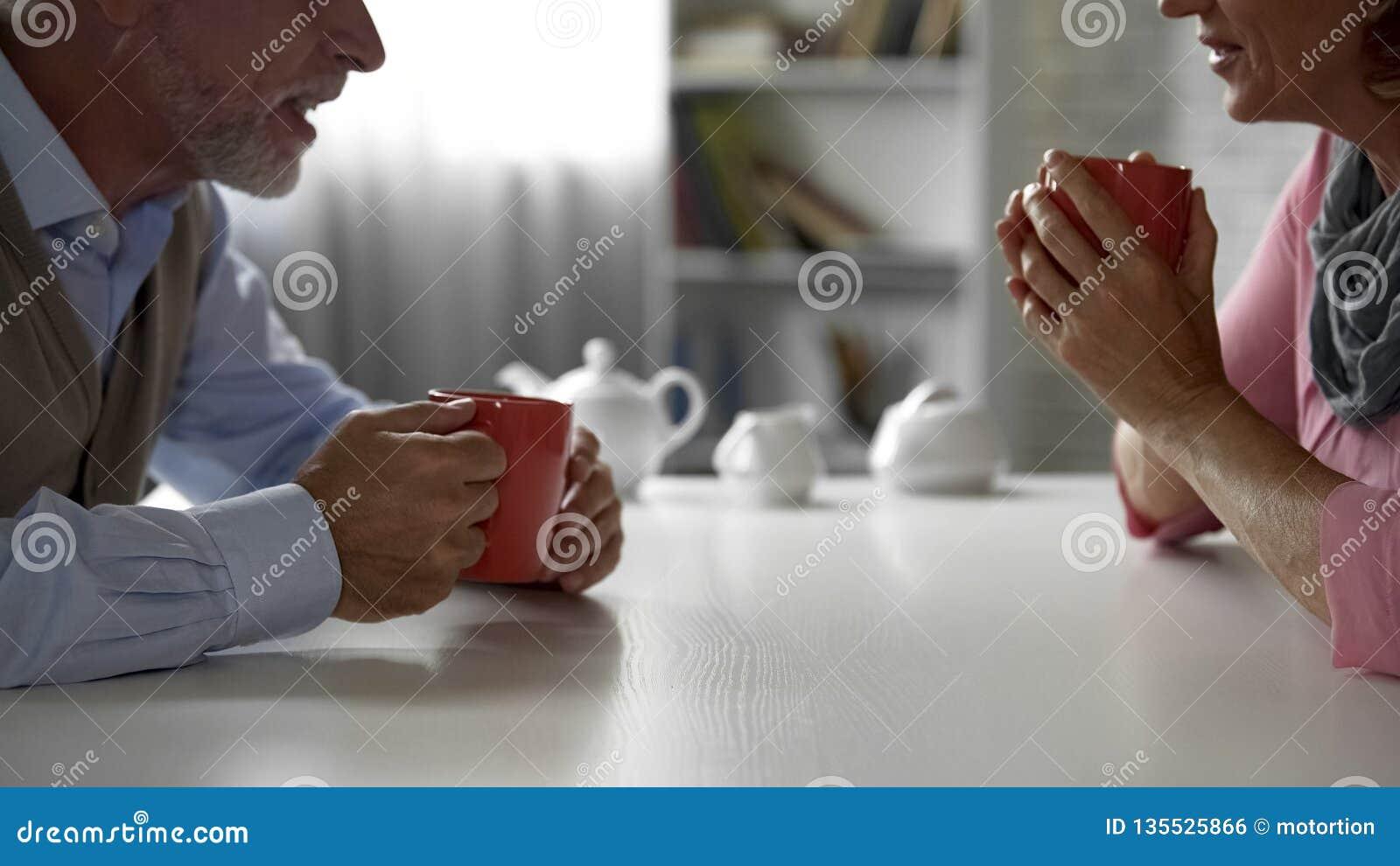 Пожилой человек и женщина сидя на кухонном столе, выпивая чае, счастливой паре