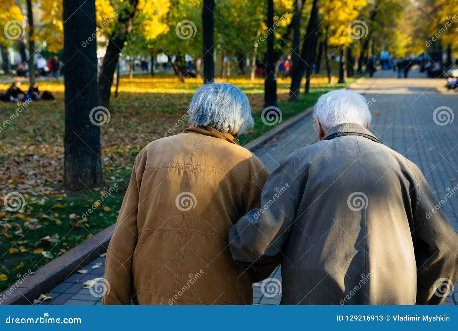 Пожилые пары идя в парк на день осени