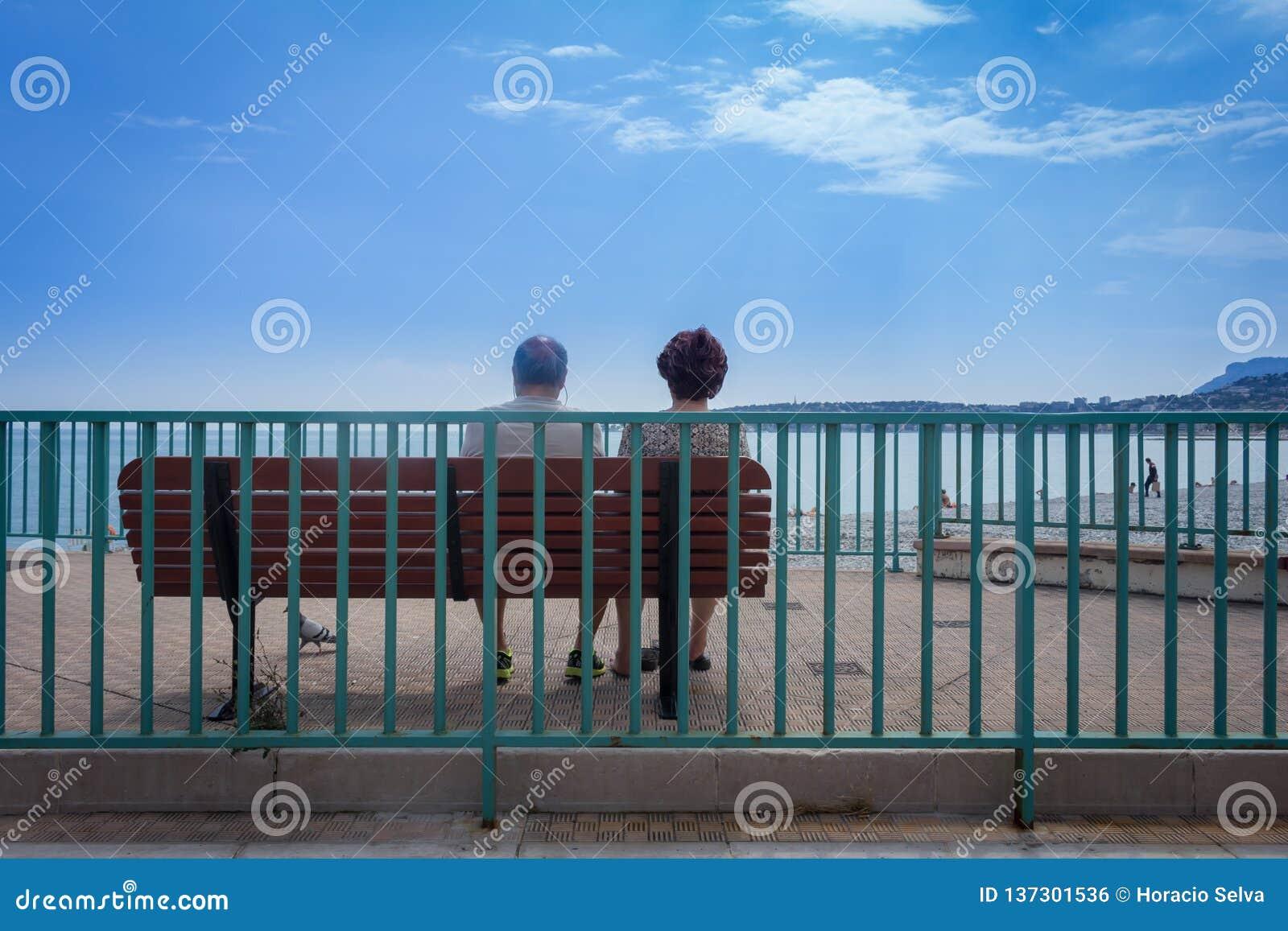 Пожилые пары сидя на стенде в площади смотря океан