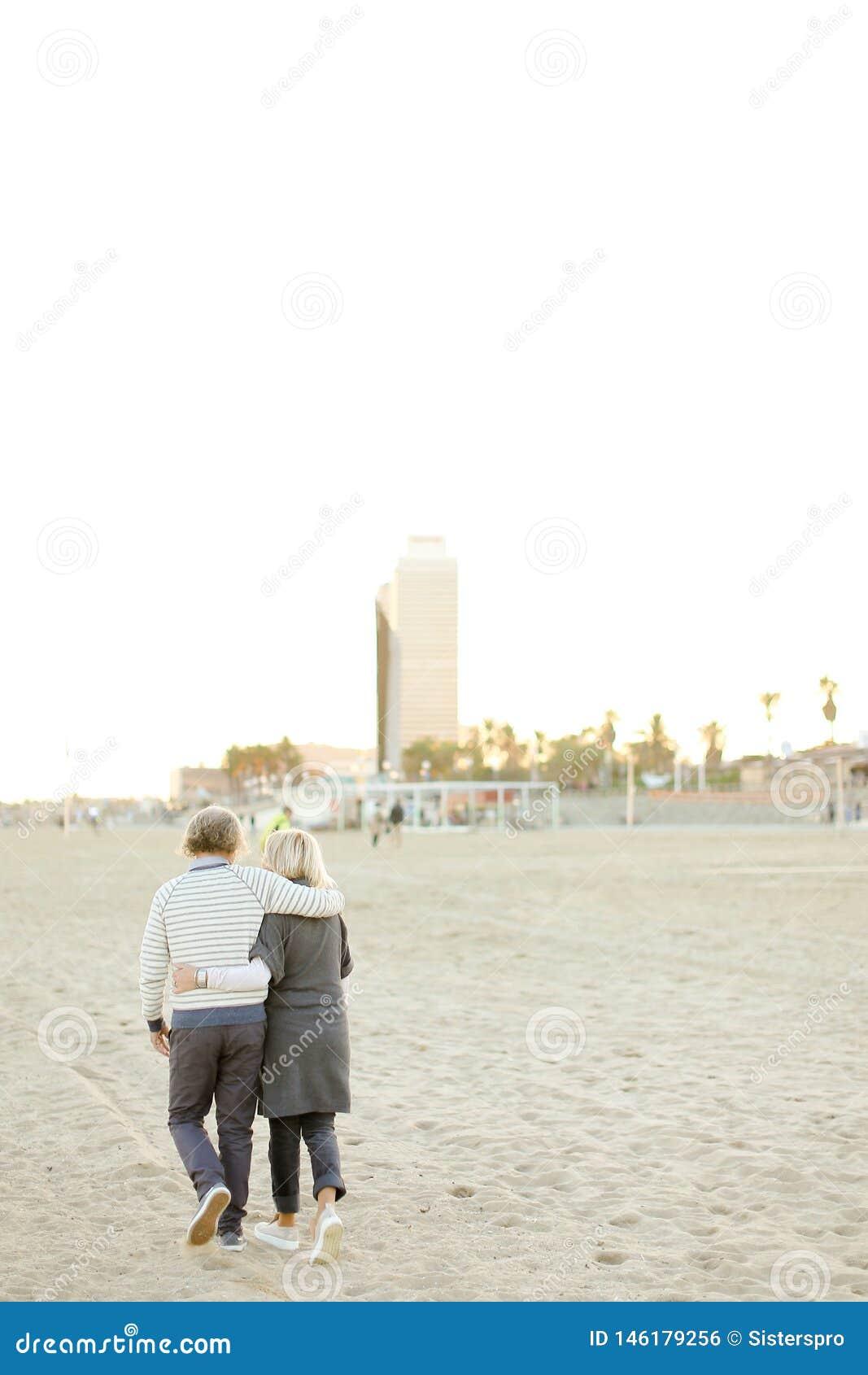 Пожилые счастливые пары идя и обнимая на пляже песка