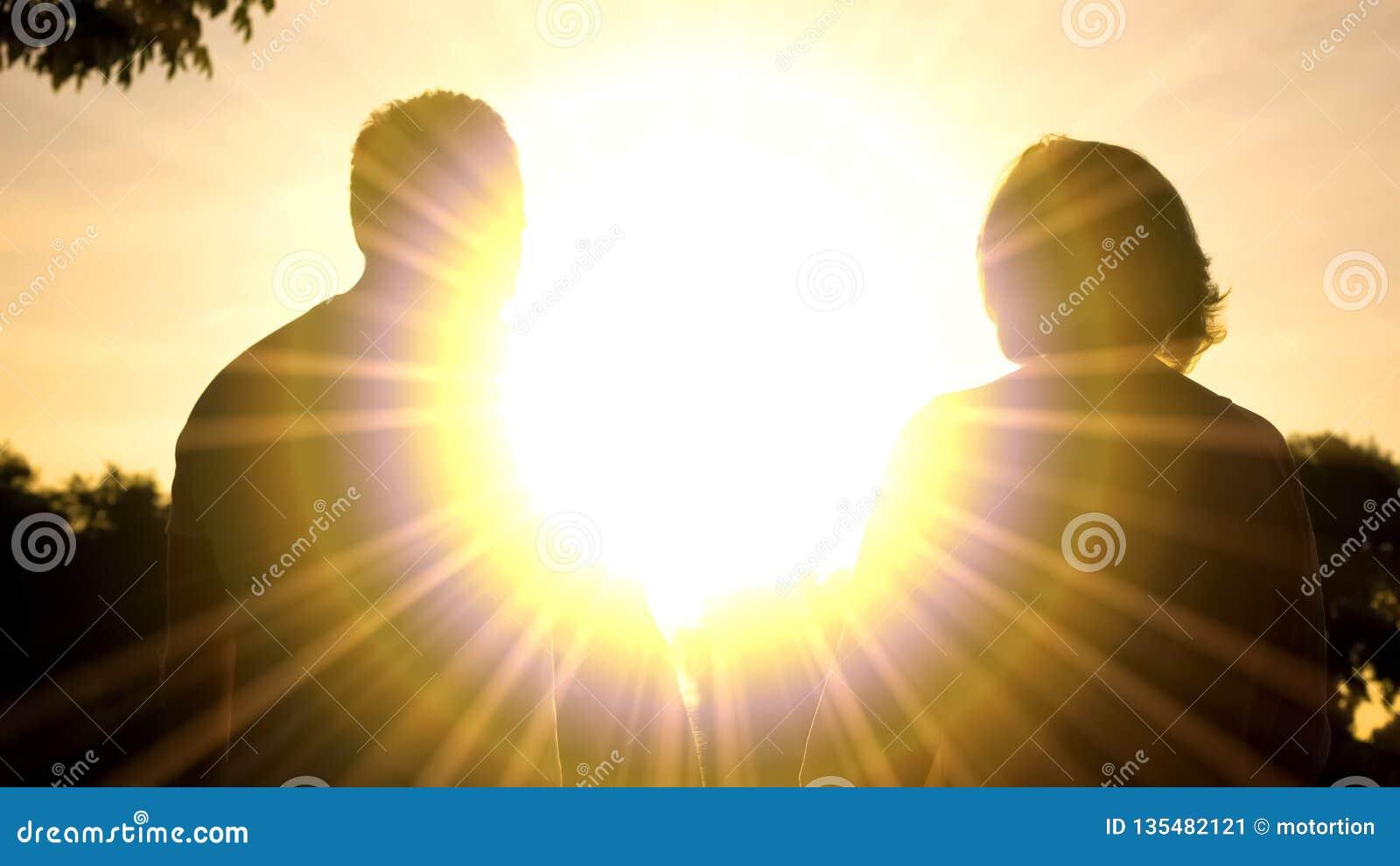 Пожилые тени в освещении захода солнца, ослабляя парк супруга и жены совместно