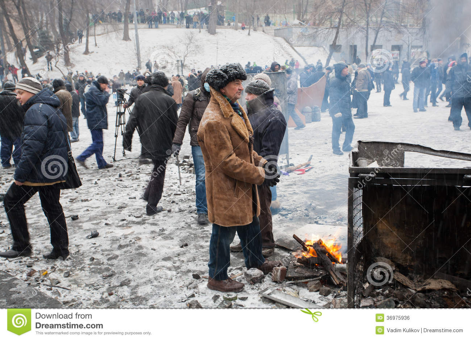 Пожилой человек в огне ожога пальто около баррикад на идя снег улице во время 2 месяцев антипровительственного протеста Euromaidan