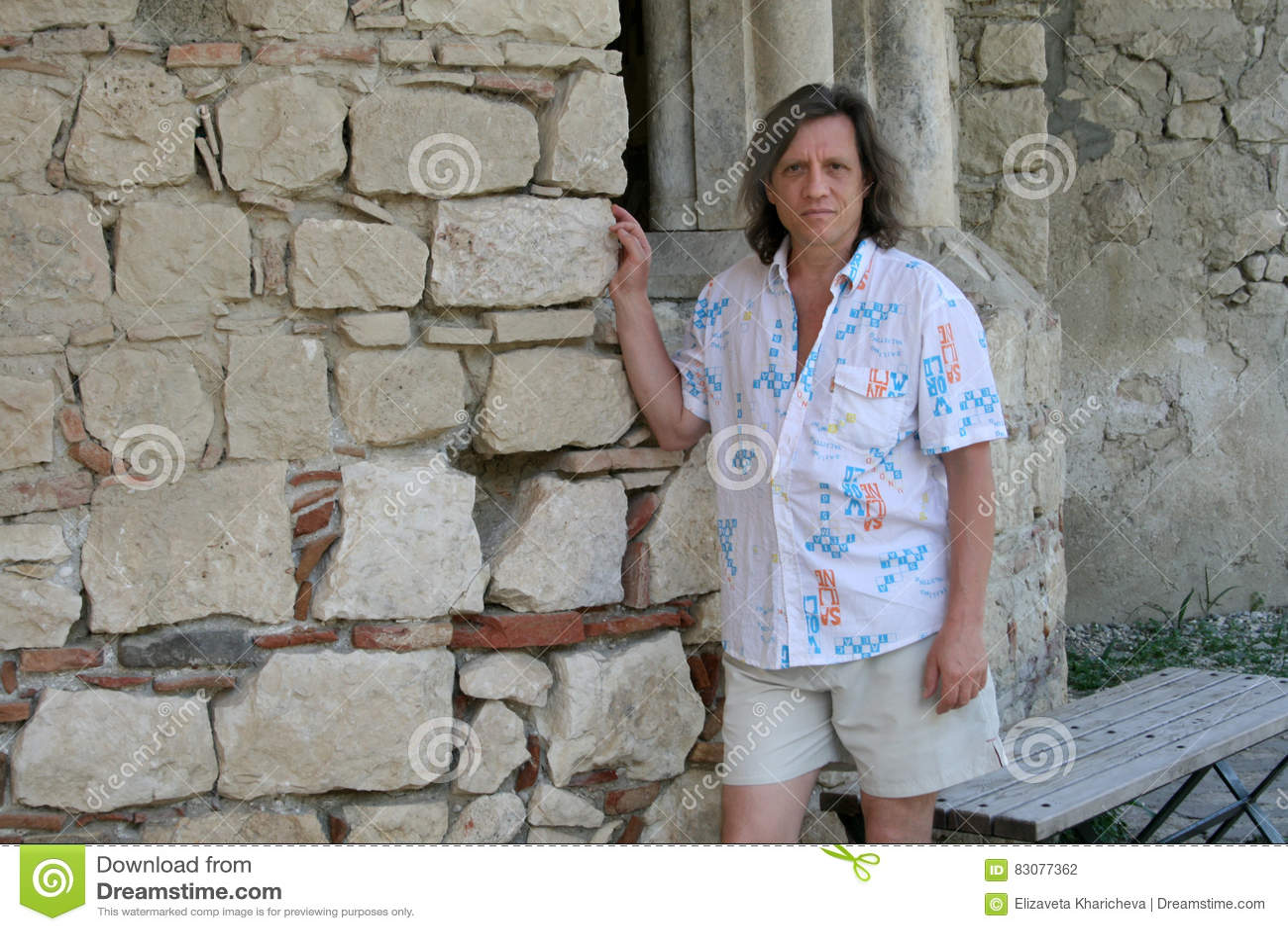 Пожилой человек около старой каменной стены