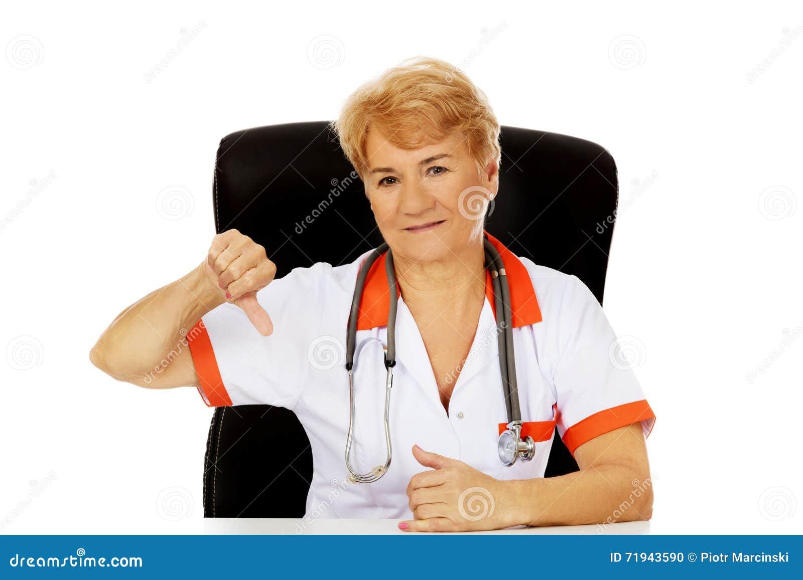 Пожилые женские доктор или медсестра сидя за столом и выставки thumb вниз