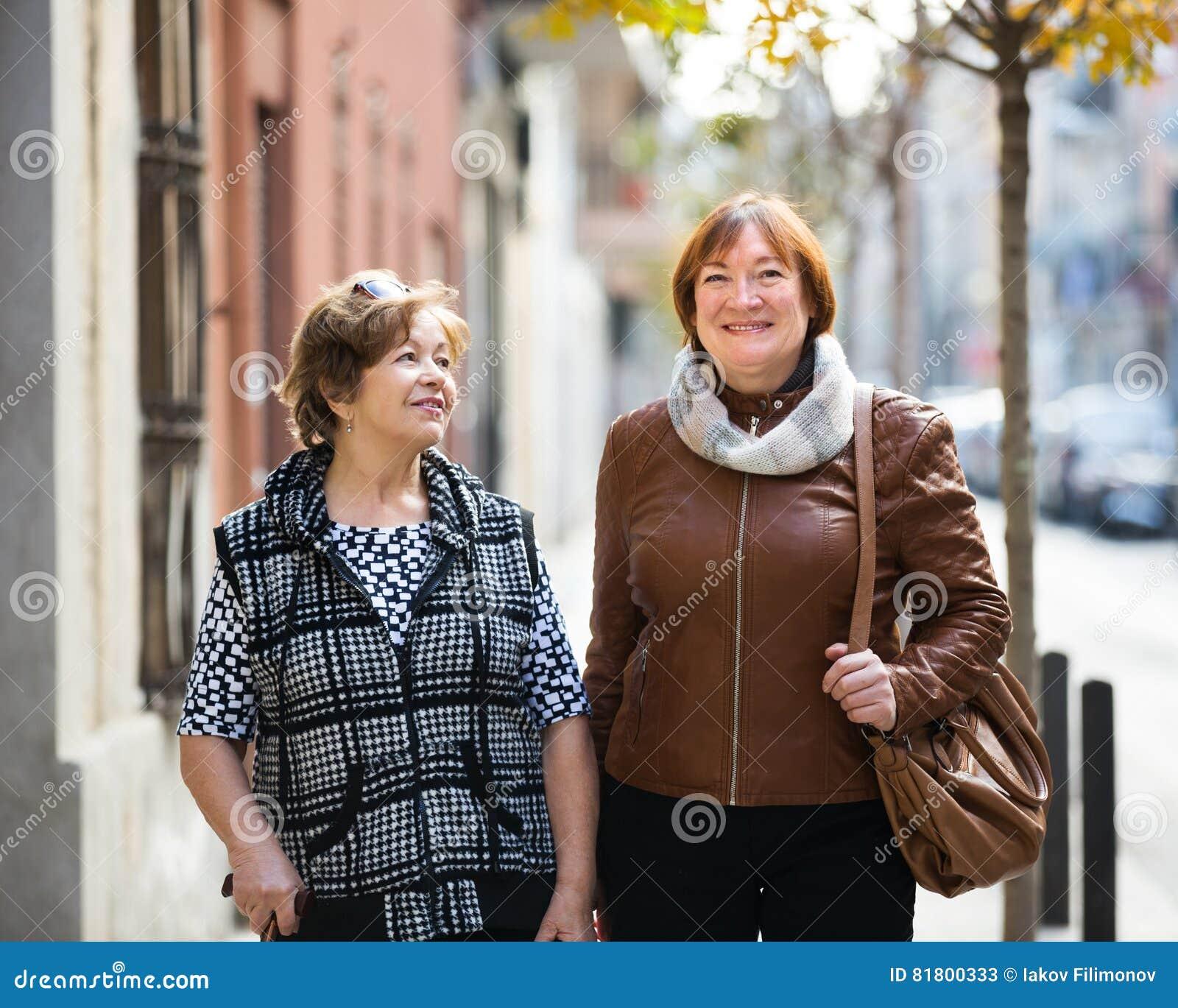 Пожилые женщины имея прогулку