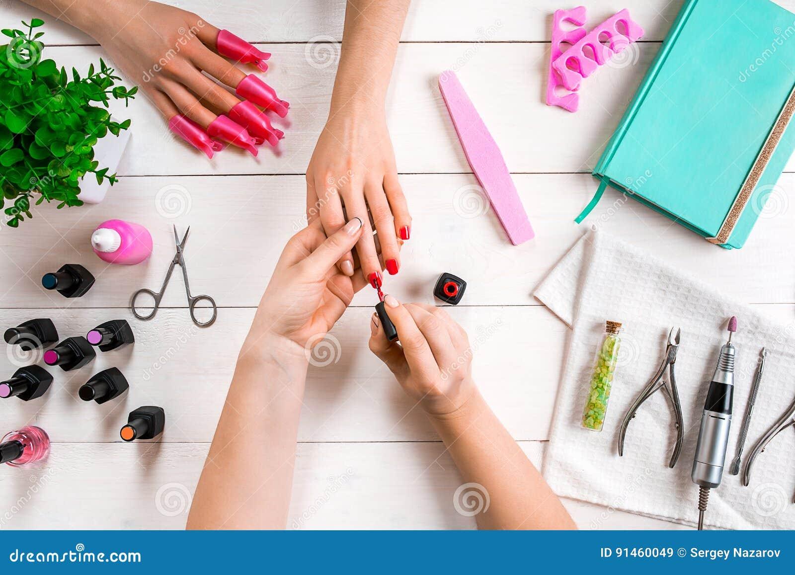 позаботьте ноготь ногтя хлопка извлекая политуру пробирки Крупный план женских рук храня ногти с профессиональной пилочкой для но