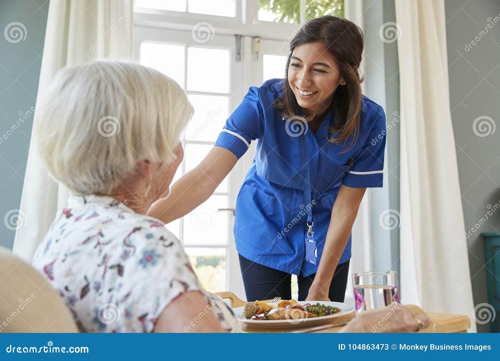 Позаботьте обедающий сервировки медсестры к старшей женщине дома