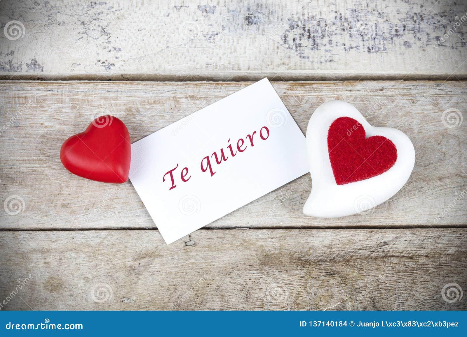 Поздравительная открытка Валентайн на деревянном столе с текстом написанным в испанском quiero Te, которое значит я тебя люблю