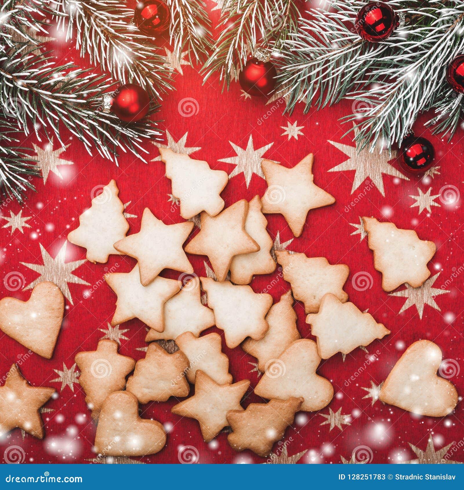 Поздравительная открытка Xmas, красная предпосылка с звездами с печеньями различных форм Ветви ели с красными шариками