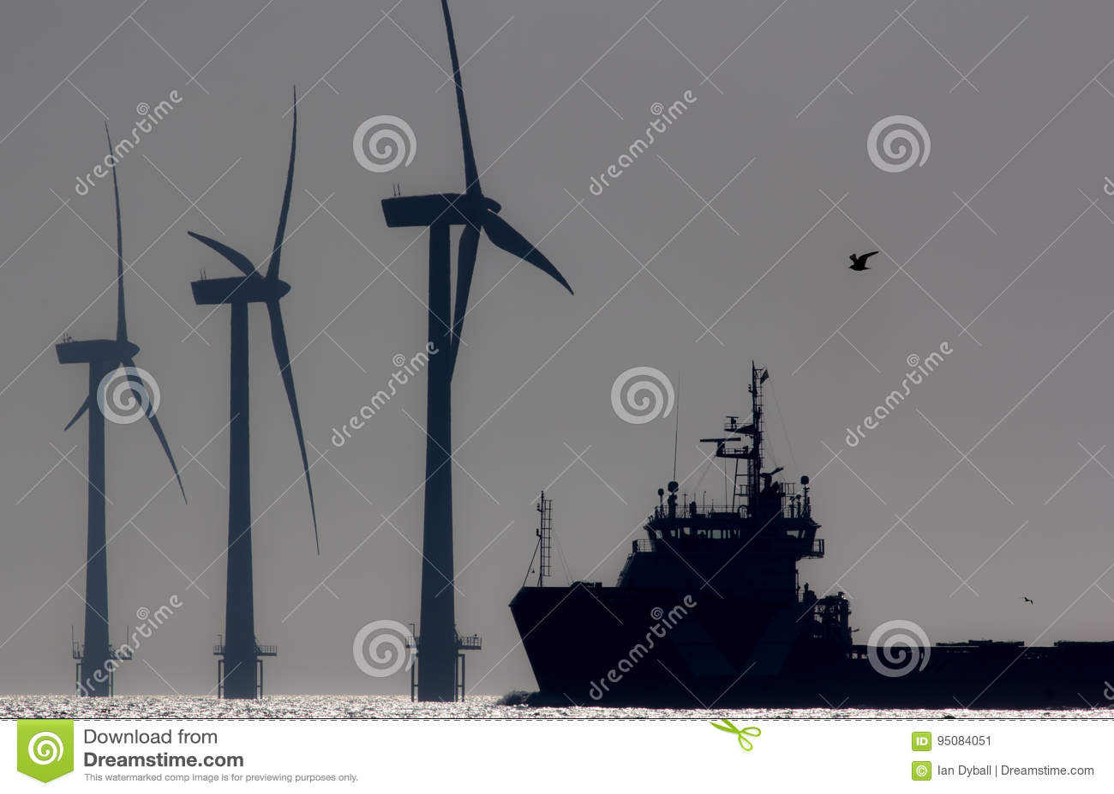 Позеленейте энергию Турбины фермы ветера с суши с кораблем на море Silh
