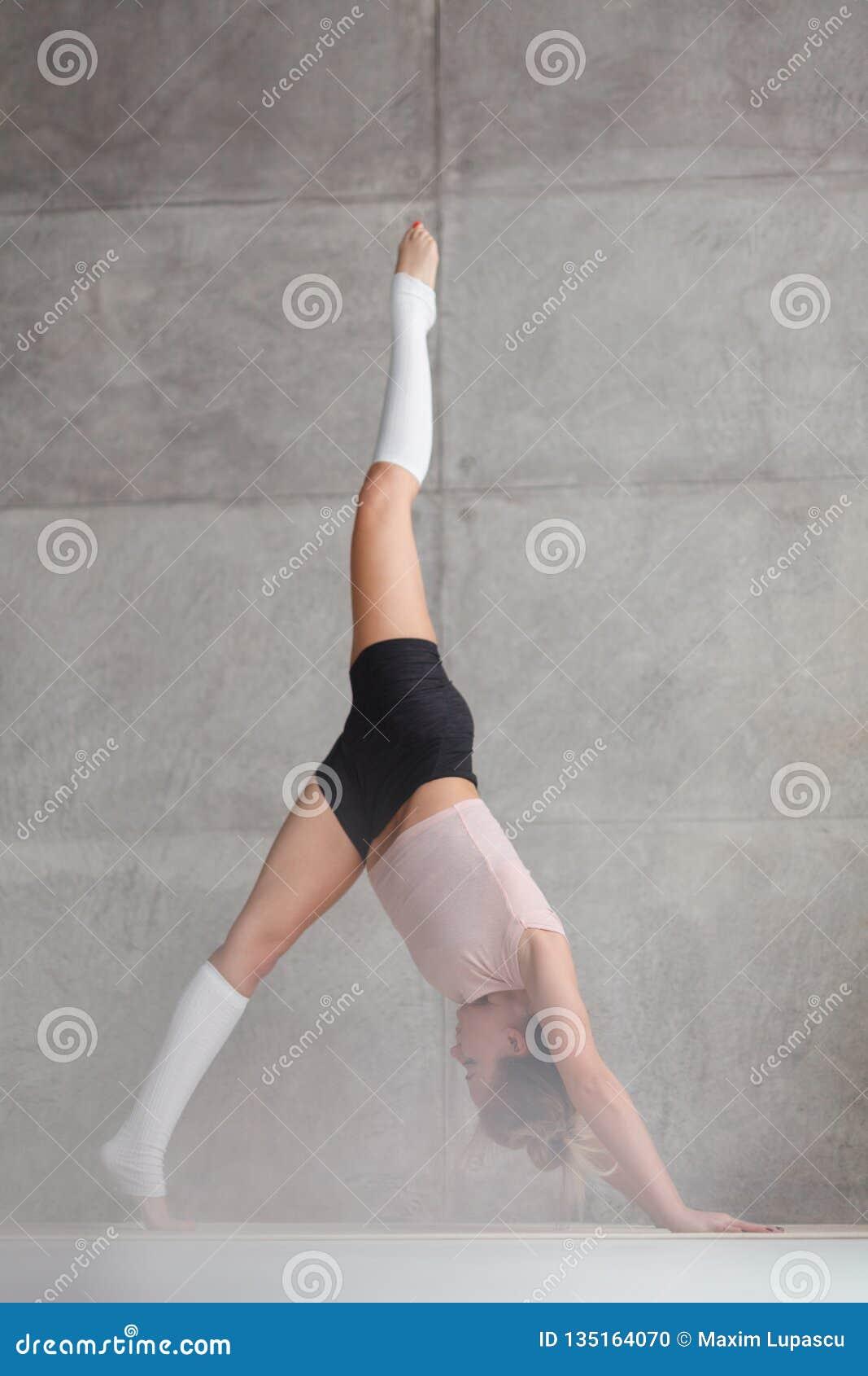 Позиция собаки вниз-облицовки Sportive женщины практикуя