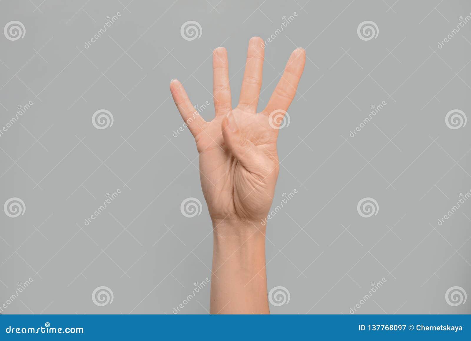 Показ 4 женщины на серой предпосылке Язык жестов