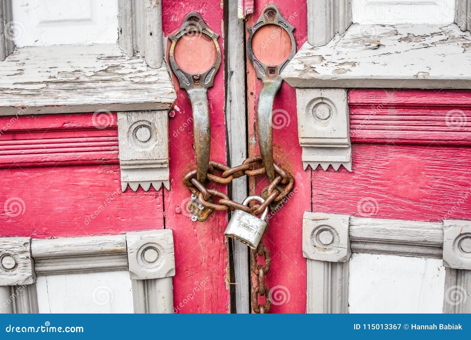 Покинутые красные двери церков с цепью и замком