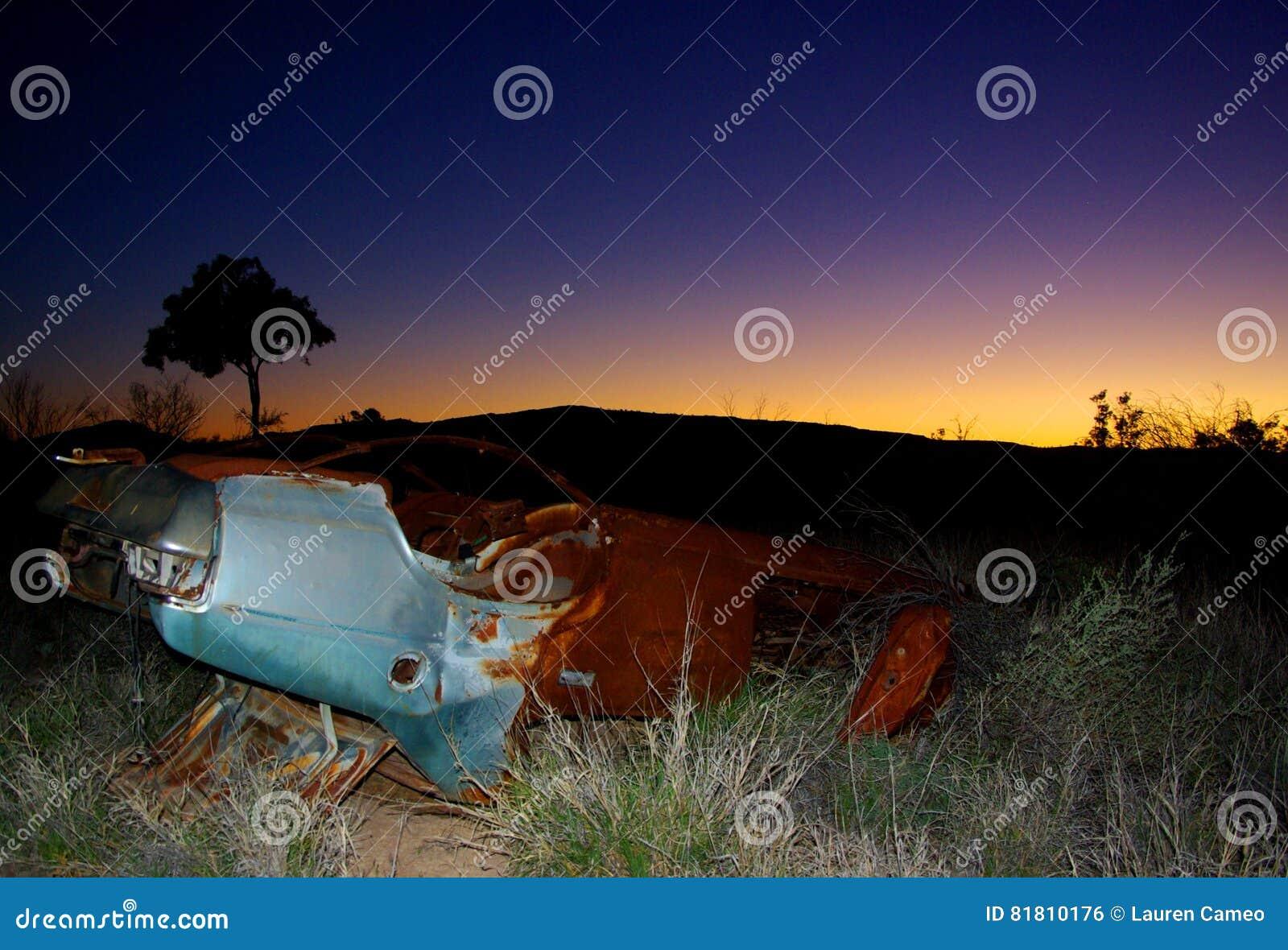 Покинутый автомобиль, заход солнца захолустья