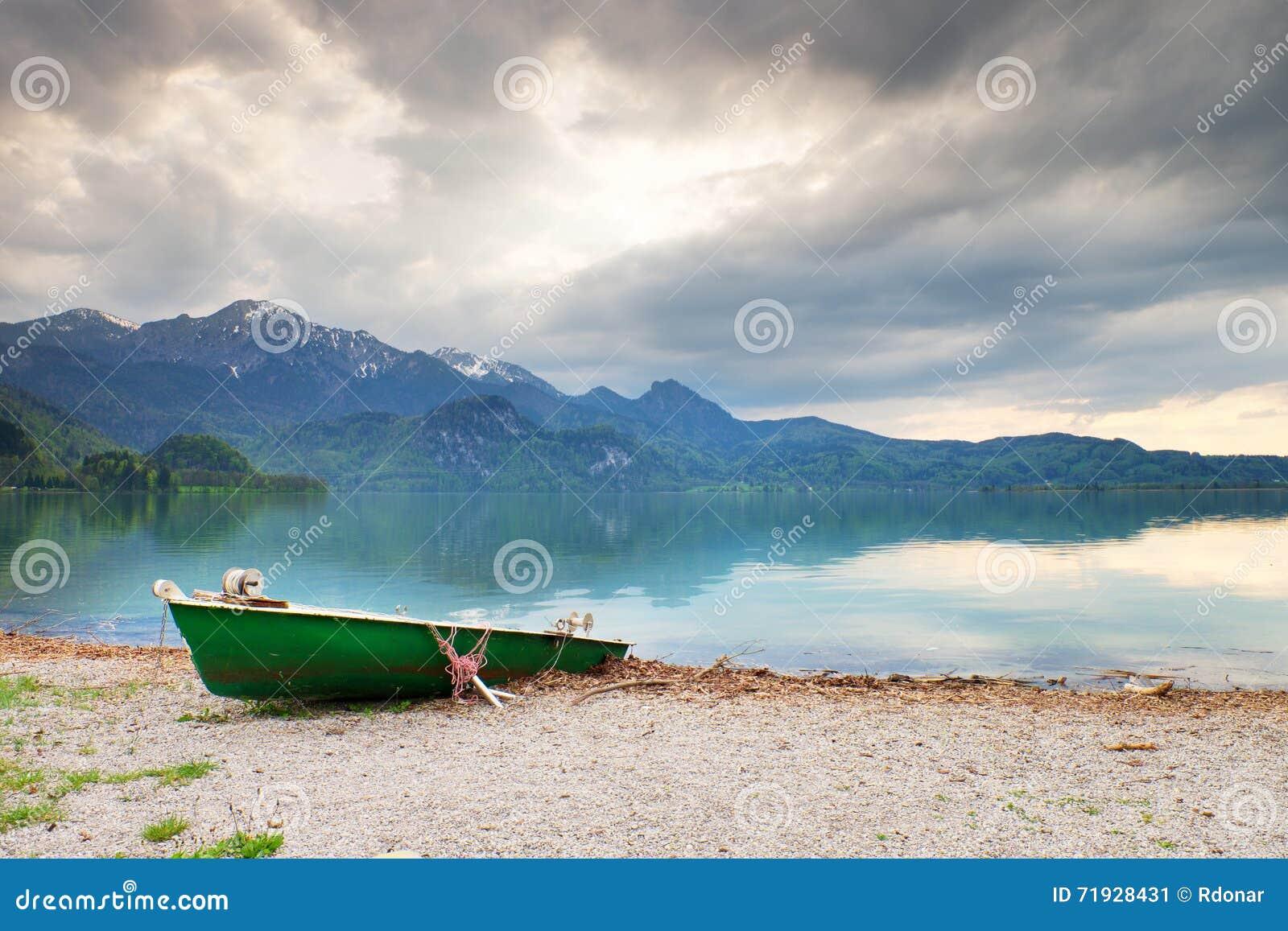 Покинутый удящ шлюпку затвора на банке озера Альп Озеро утр накаляя солнечным светом