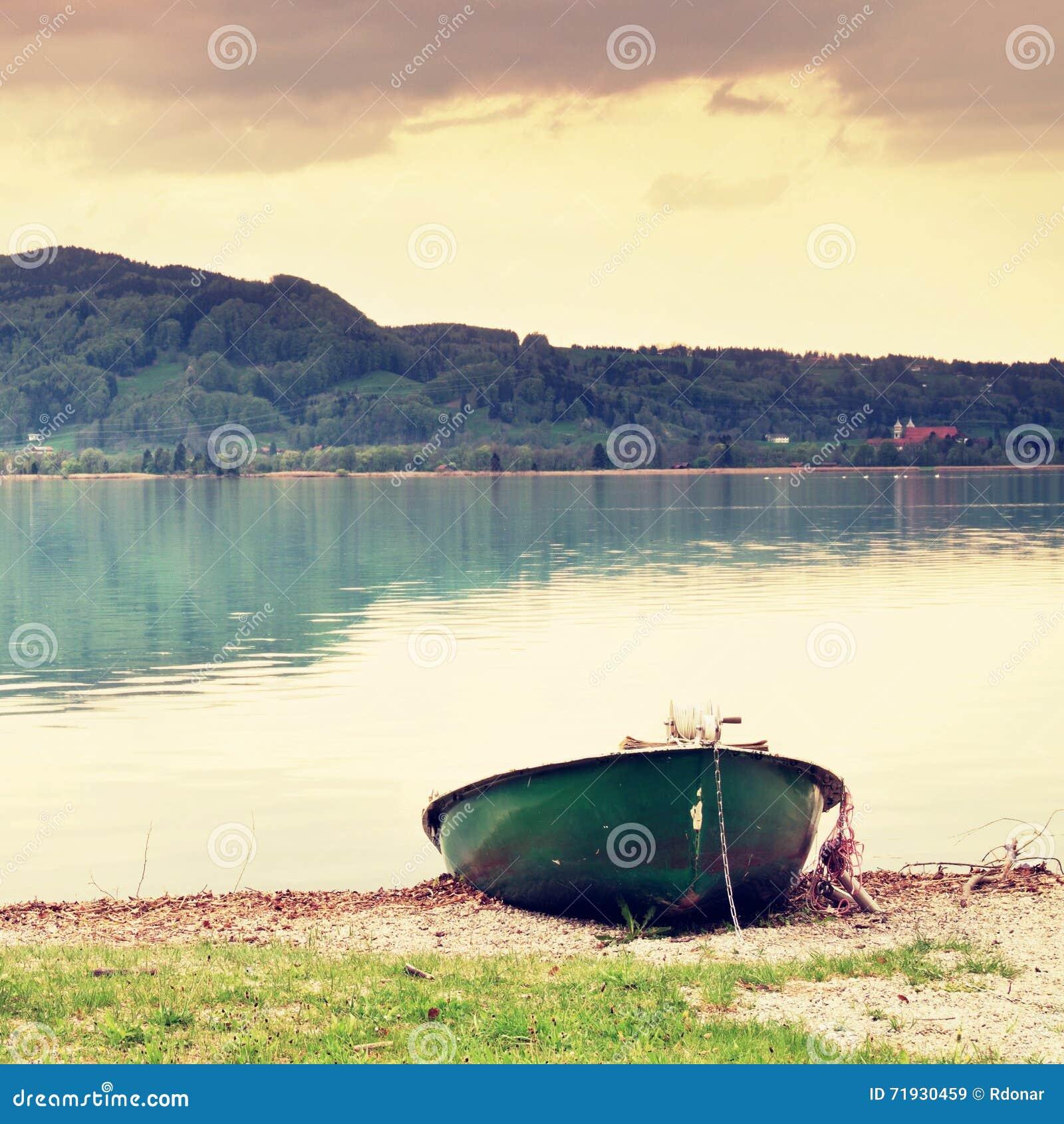 Покинутый удящ шлюпку затвора на банке Озеро Альп утра