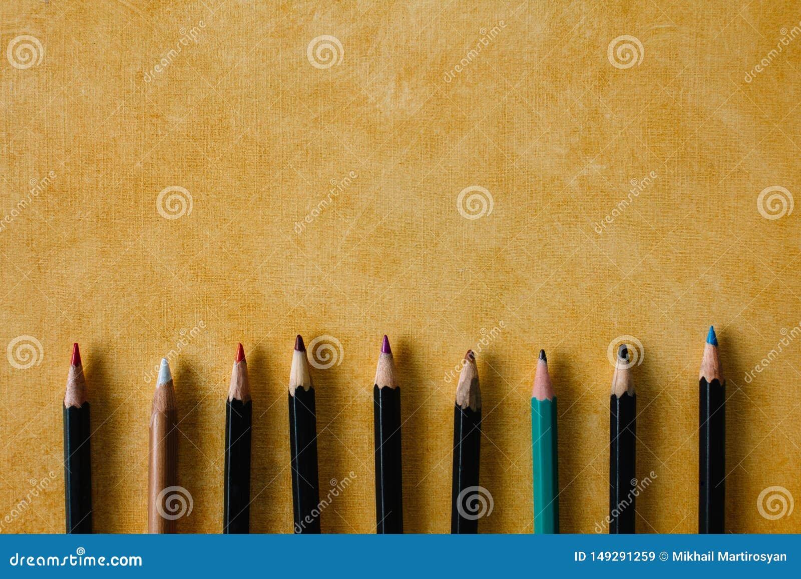 Покрашенные карандаши на текстурной бумажной предпосылке желтого космоса экземпляра цвета