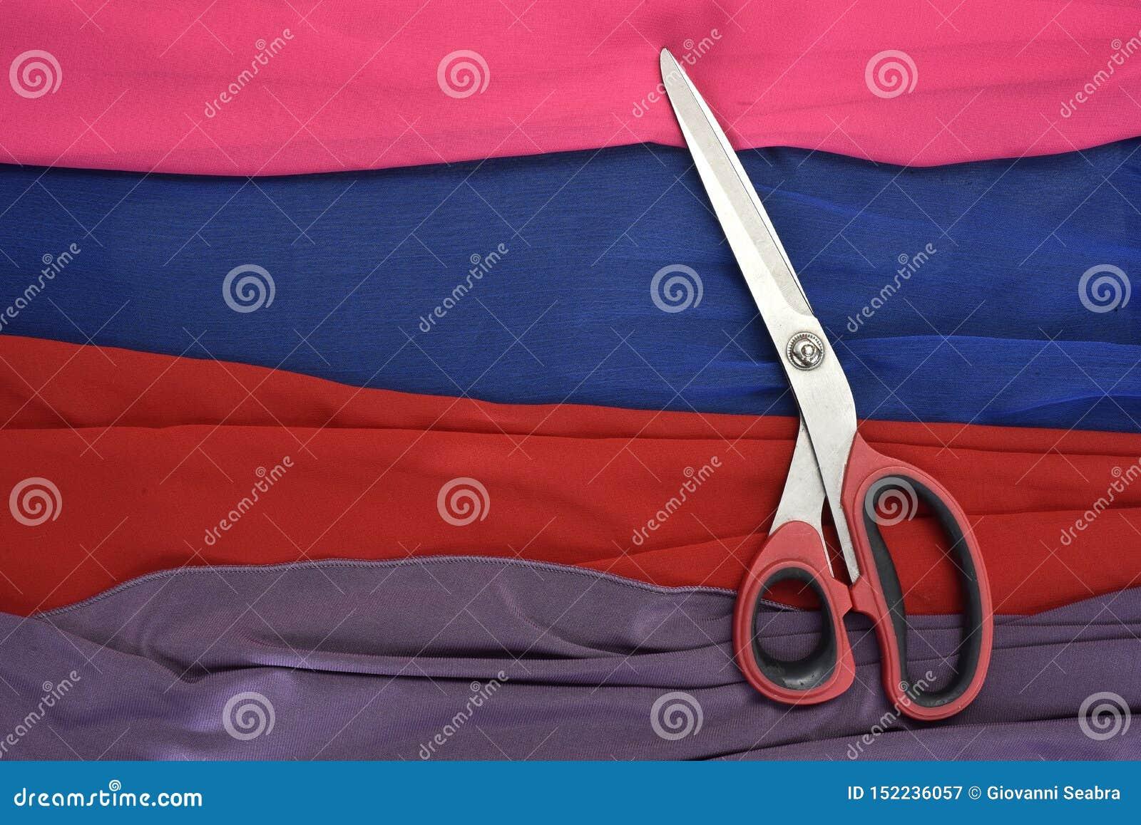 Покрашенные ткани отрезанные с ножницами
